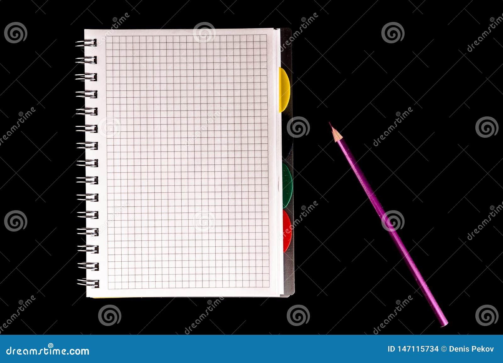 Lápis da cor e caderno, isolado no fundo preto