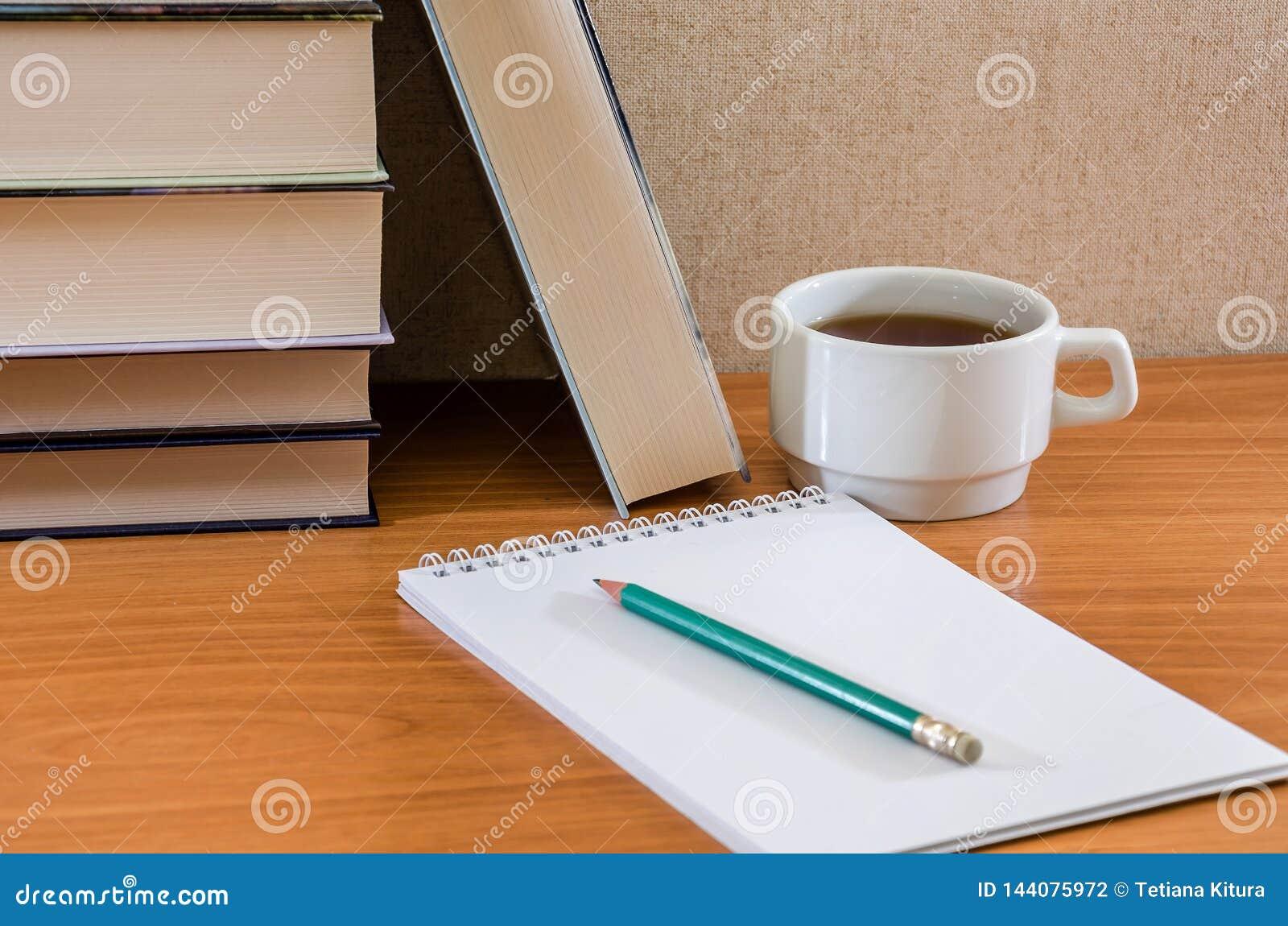 Lápiz en un cuaderno, libros y una taza de té en la tabla