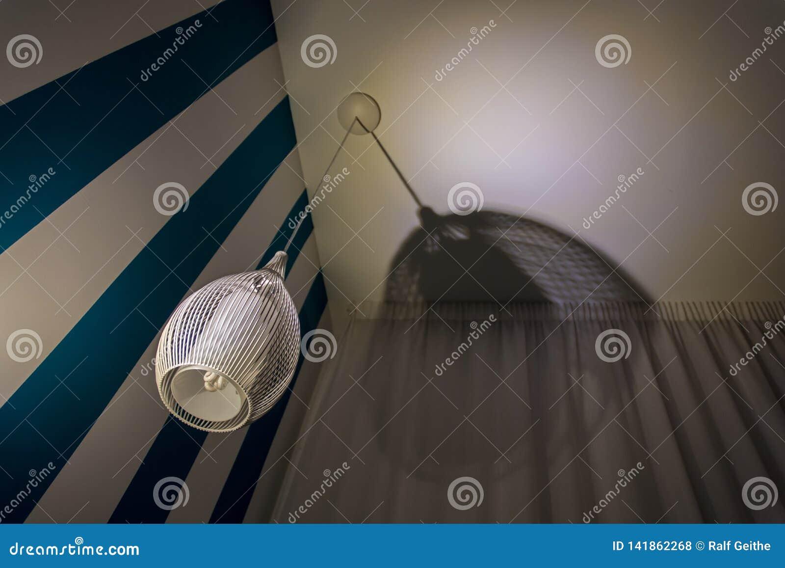 Lâmpada à moda do teto ao lado da parede branca azul com cortina