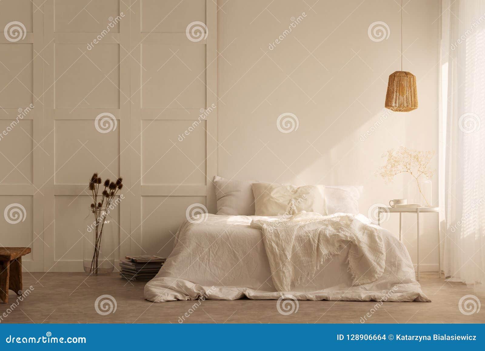 Lâmpada acima da cama branca com os descansos no interior mínimo do quarto com plantas e tamborete