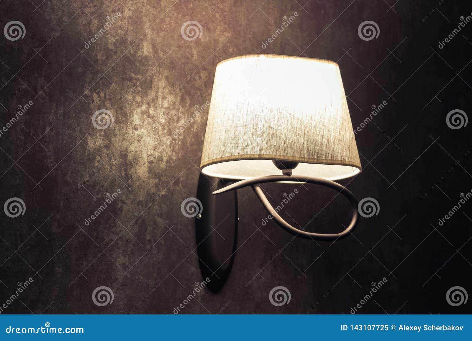 Lâmpada branca original, candelabro de parede em uma parede marrom no estilo do vintage
