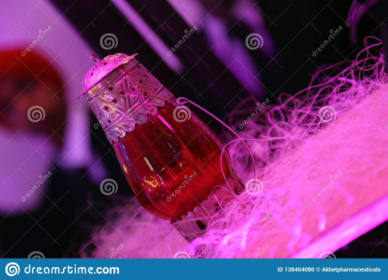 Lâmpada de vidro vermelha com o trabalho do metal isolado com fundo do borrão
