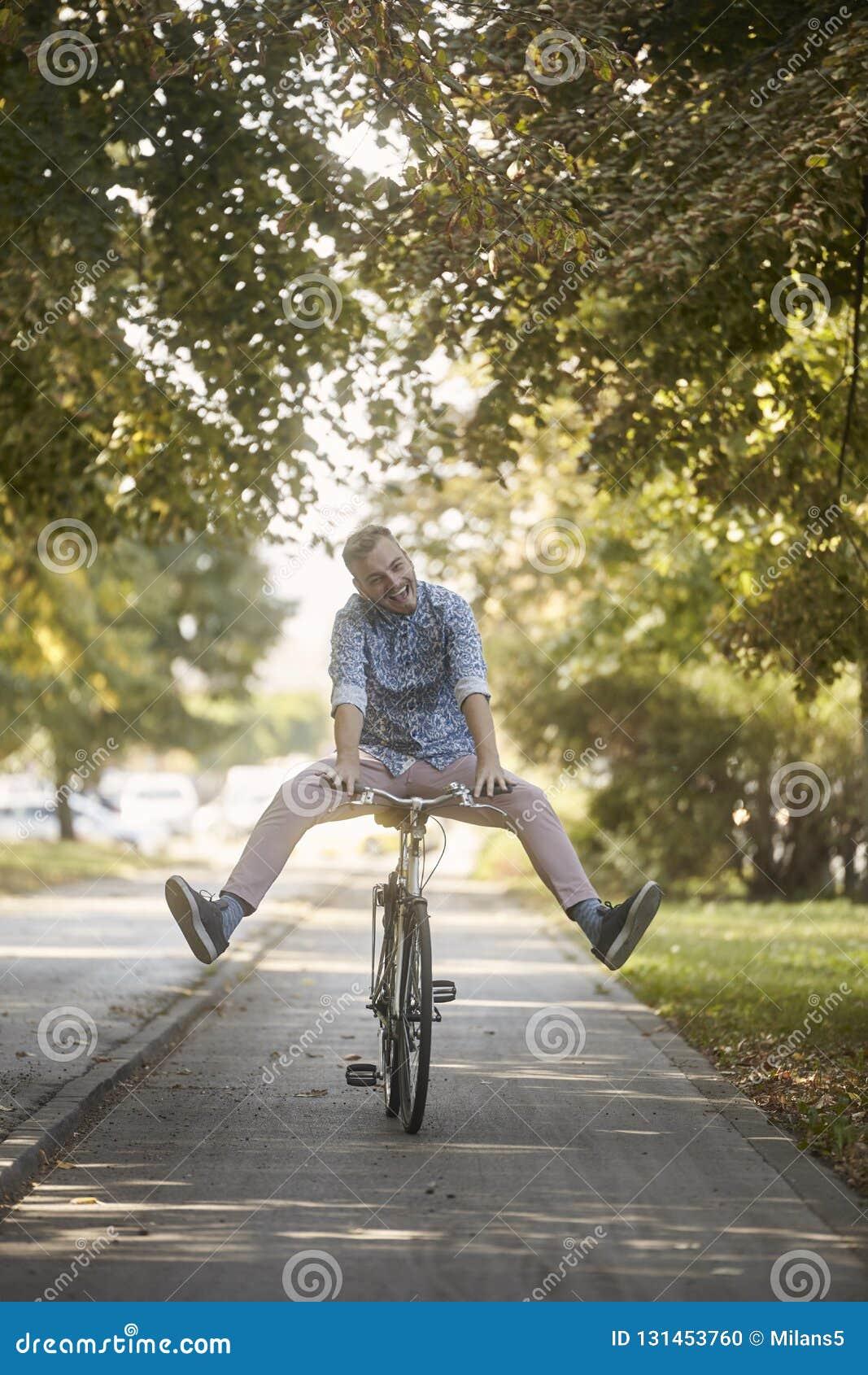 Lächeln, lustiger, lächerlicher, junger Mann, 20-29 Jahre alt, fahrend auf Straßenbahn rad Beinverbreitung