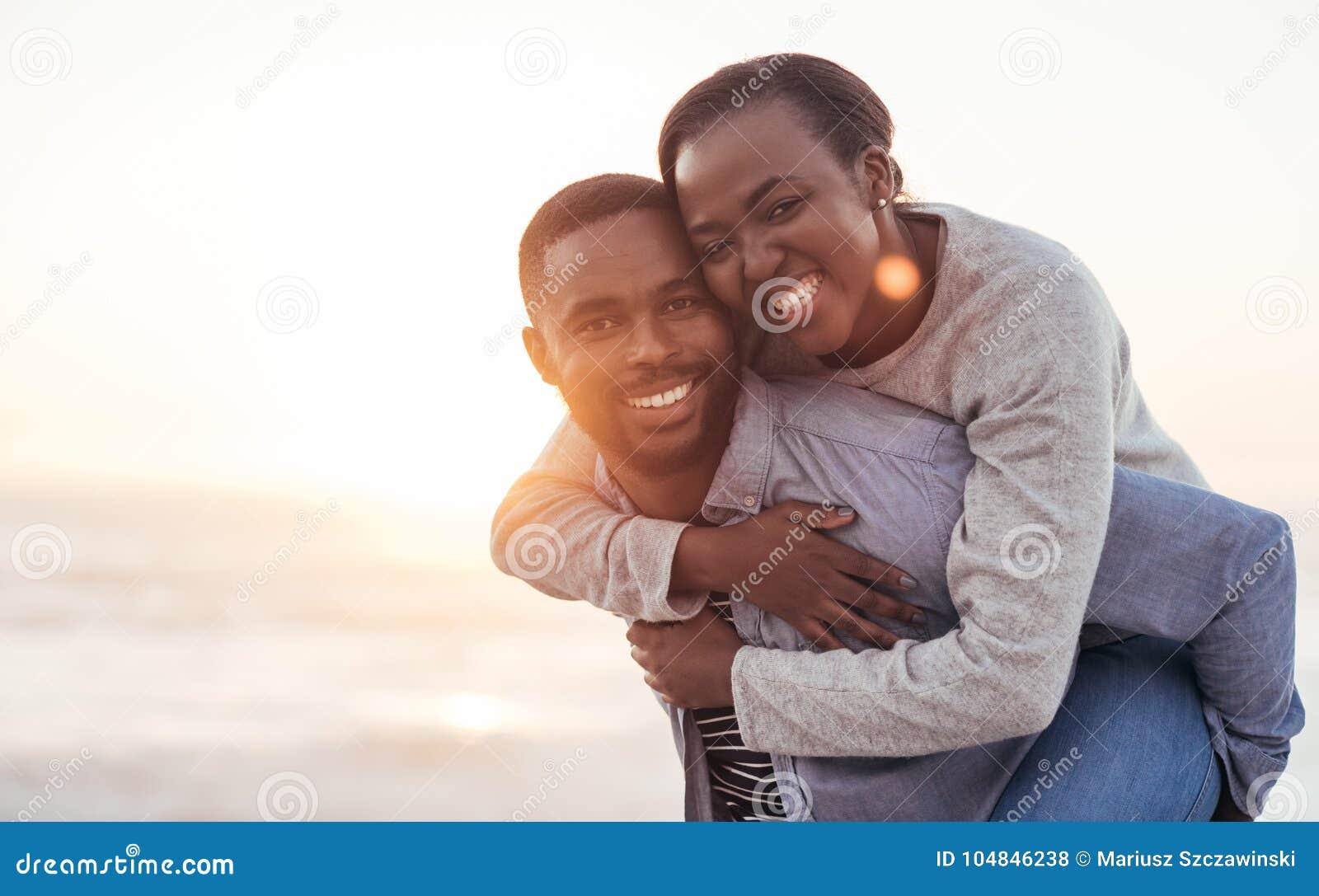 Lächelnde afrikanische Paare, die einen sorglosen Tag am Strand genießen