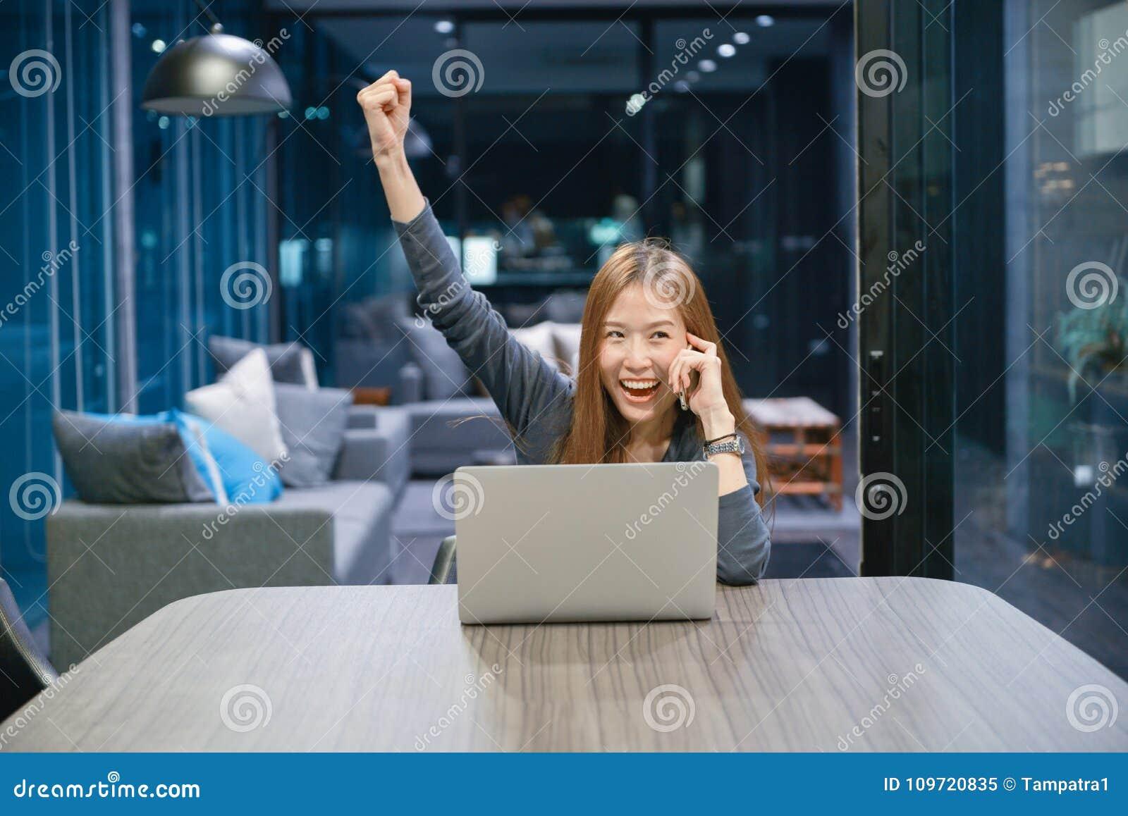 Lächelnde Asiatin, die am Telefon, unter Verwendung des Laptops nachts spricht,