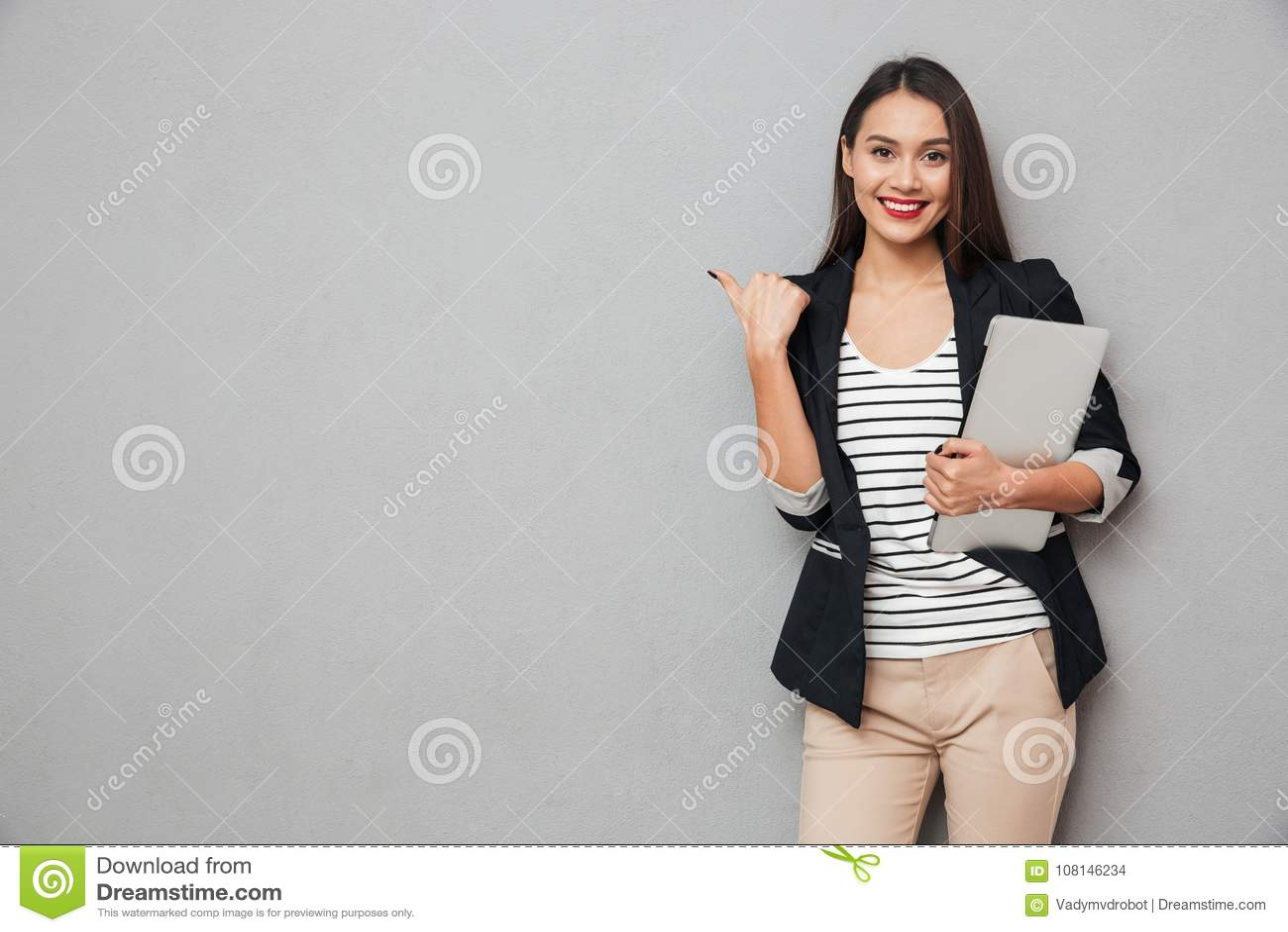 Lächelnde asiatische Geschäftsfrau, die Laptop-Computer hält und weg zeigt