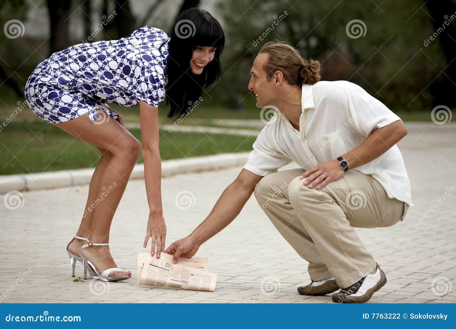Lächelnde attraktive Paarsitzung im Sommerpark