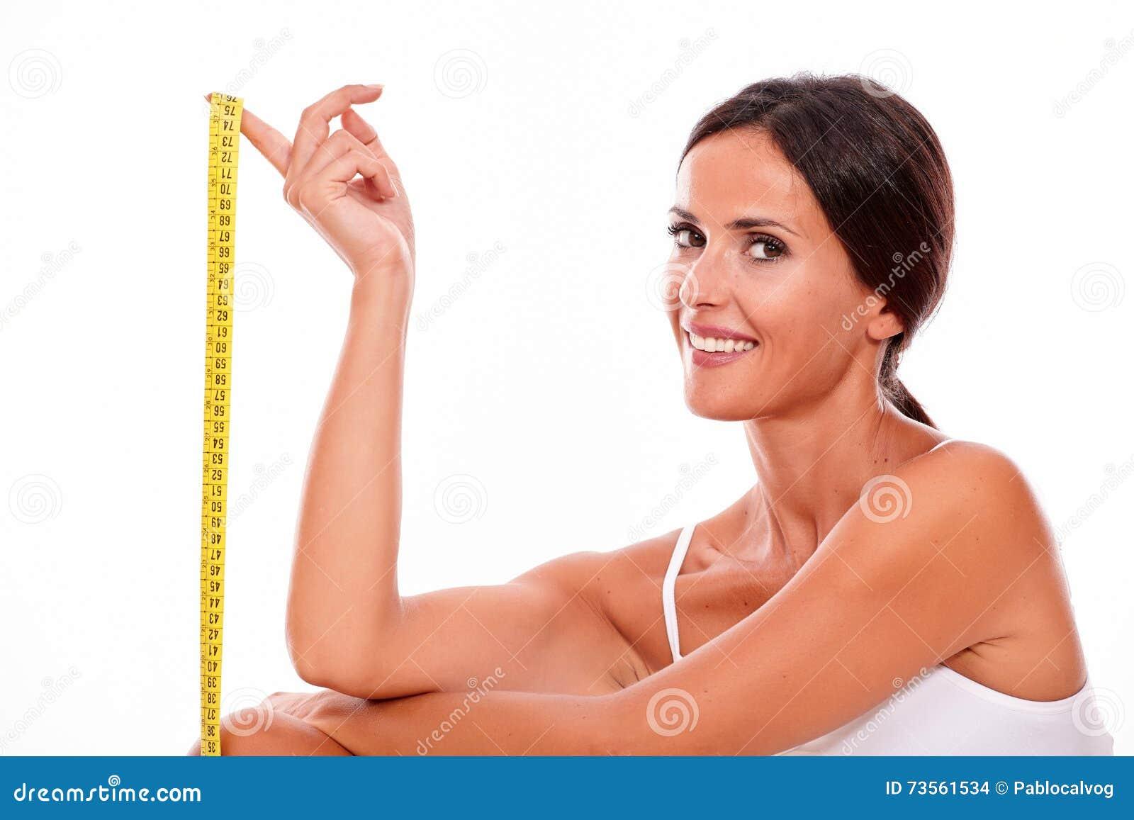 Lächelnde Brunettefrau mit Maßband