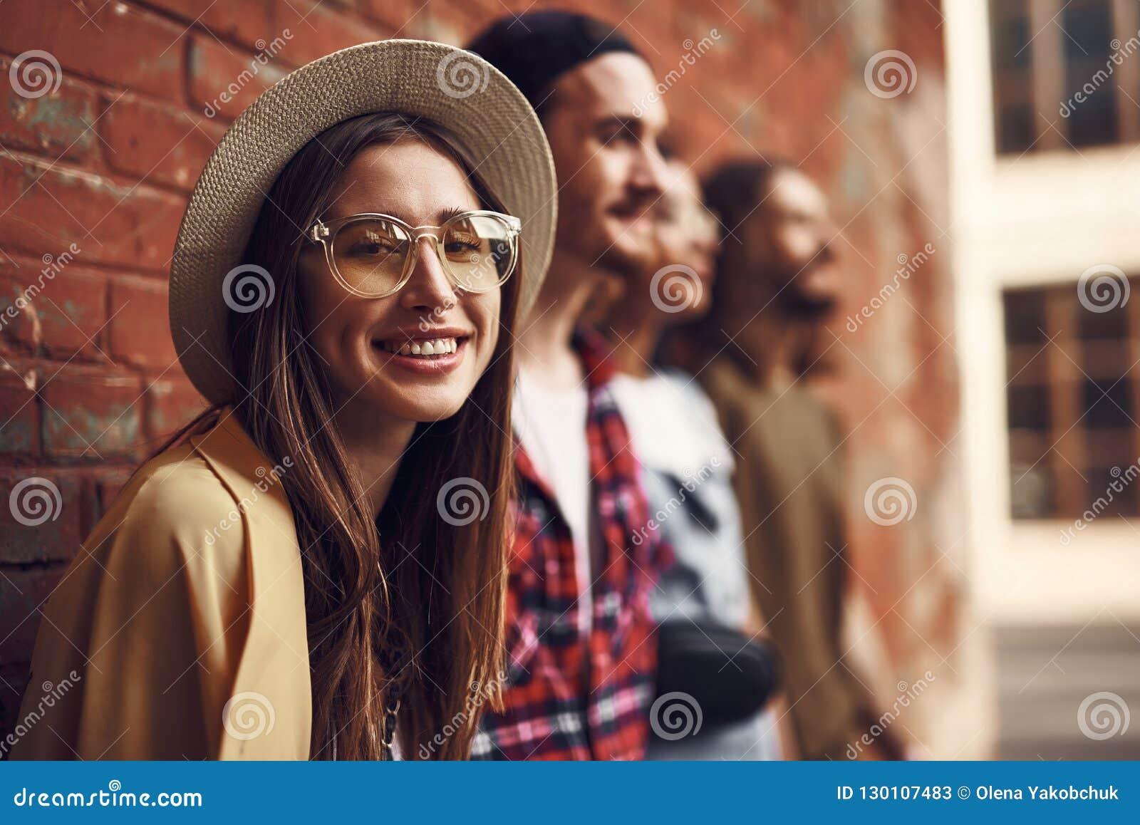 Lächelnde Dame, die Sie bei der Stellung nahe ihren Freunden betrachtet