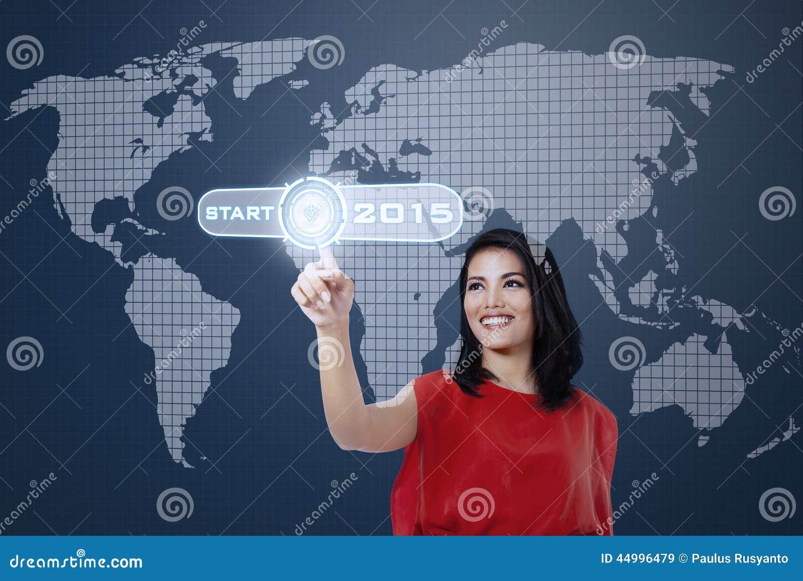 Lächelnde Frau, die einen Startknopf berührt
