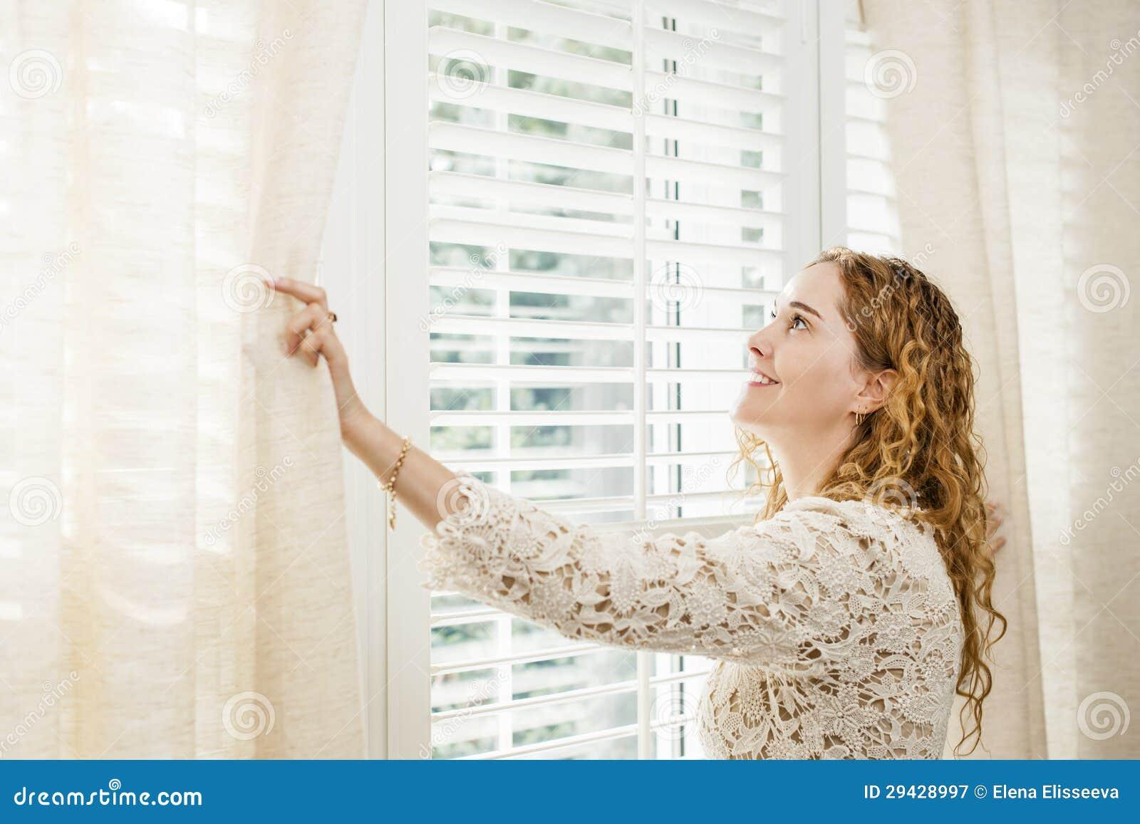Lächelnde Frau, die heraus Fenster schaut