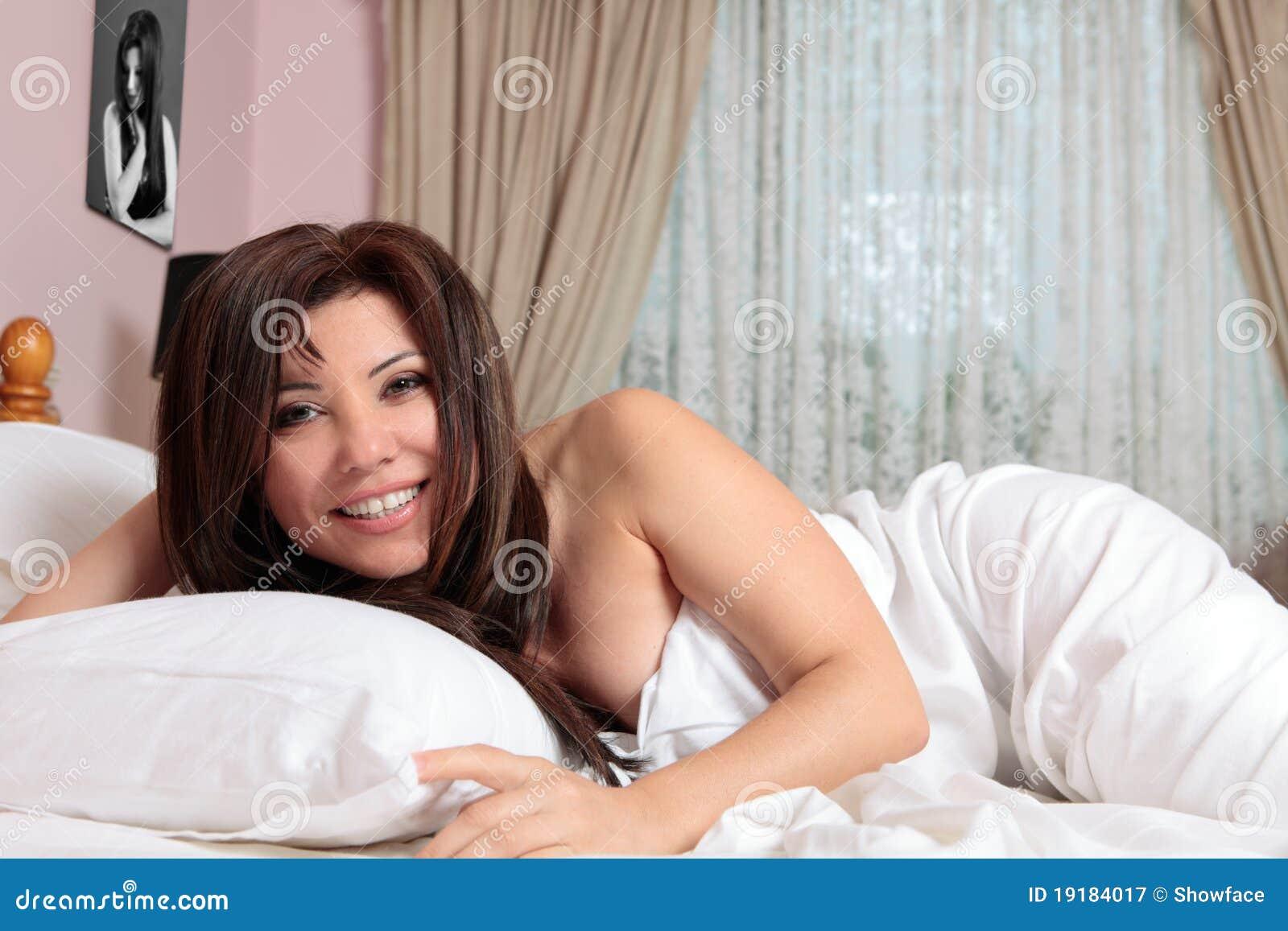 Lächelnde Frau, die im Bett sich entspannt
