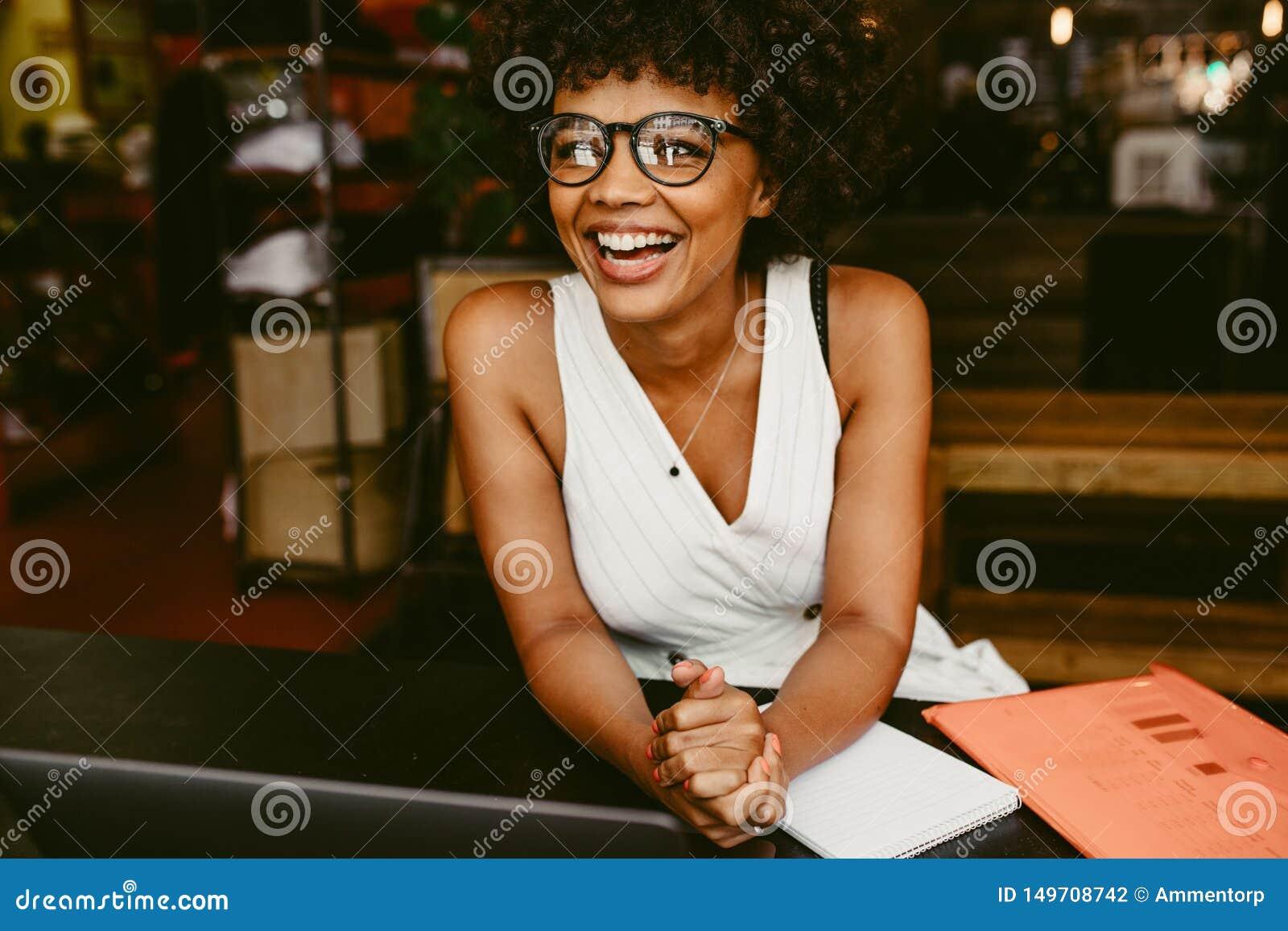 Lächelnde Frau, die im Café sitzt