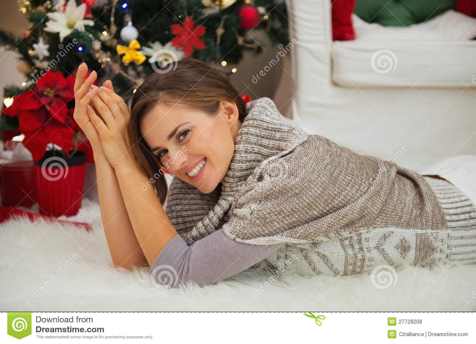 Lächelnde Frau, die nahe Weihnachtsbaum legt