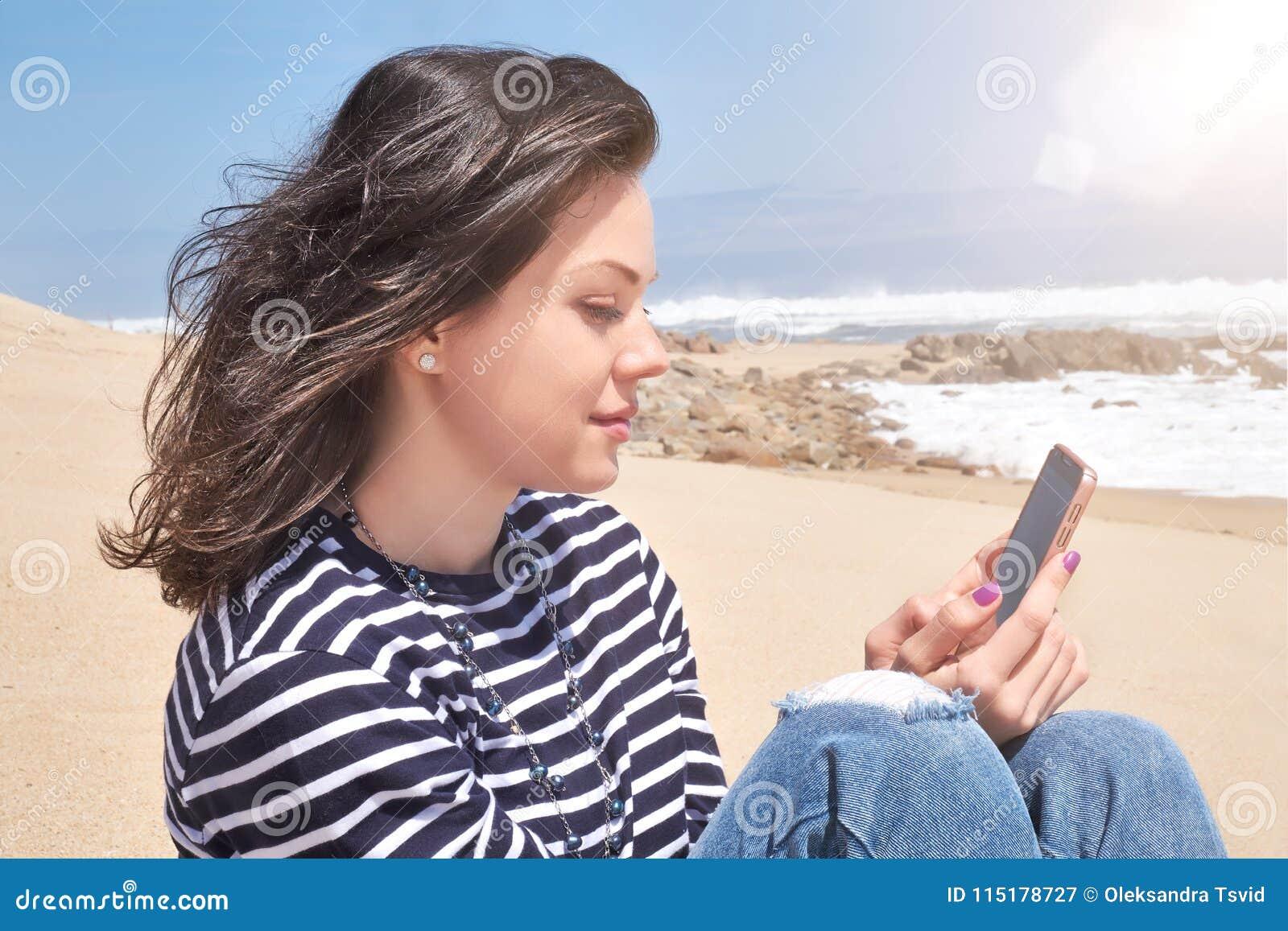 Lächelnde Frau in einem gestreiften T-Shirt mit dem Smartphone, der auf Strand, Sommertag sich entspannt