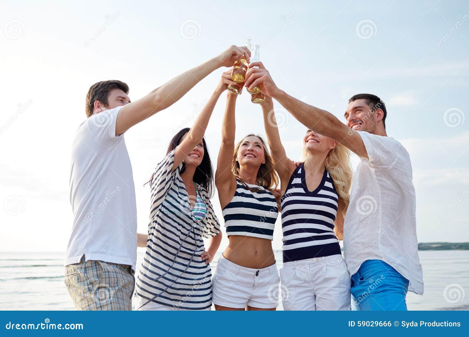 Lächelnde Freunde, die Flaschen auf Strand klirren
