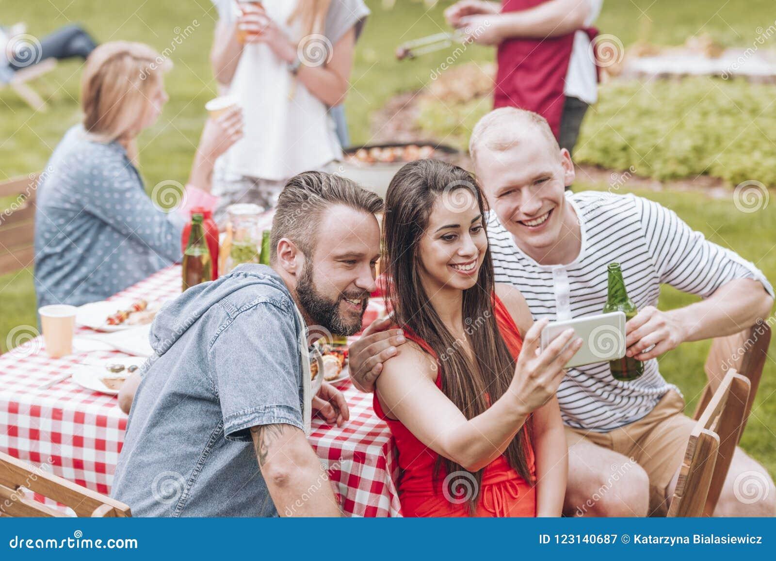 Lächelnde Freunde, die selfie während der Grillpartei im Garten nehmen