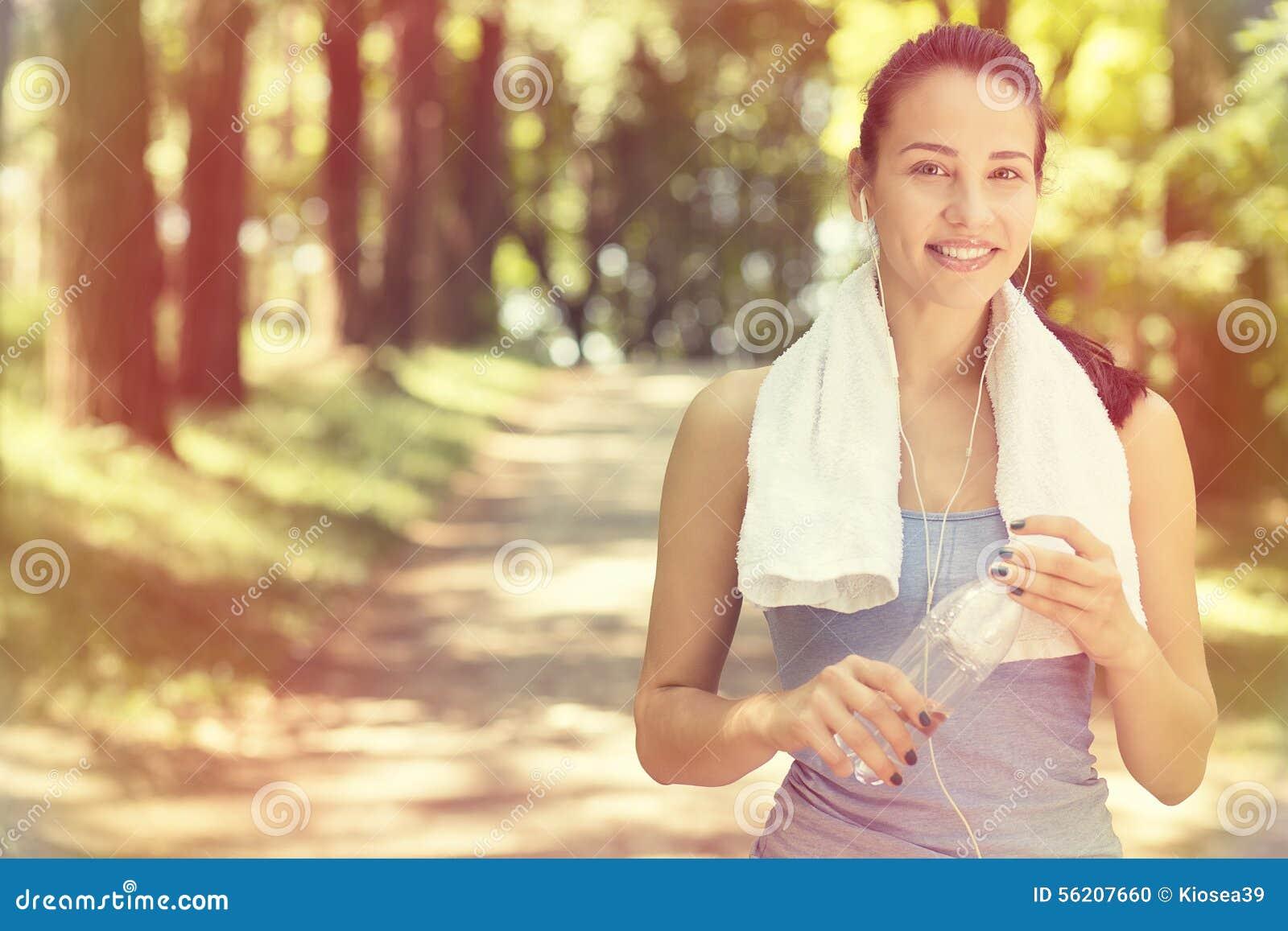 Lächelnde geeignete Frau mit dem weißen Tuch, das nach Sport stillsteht, trainiert