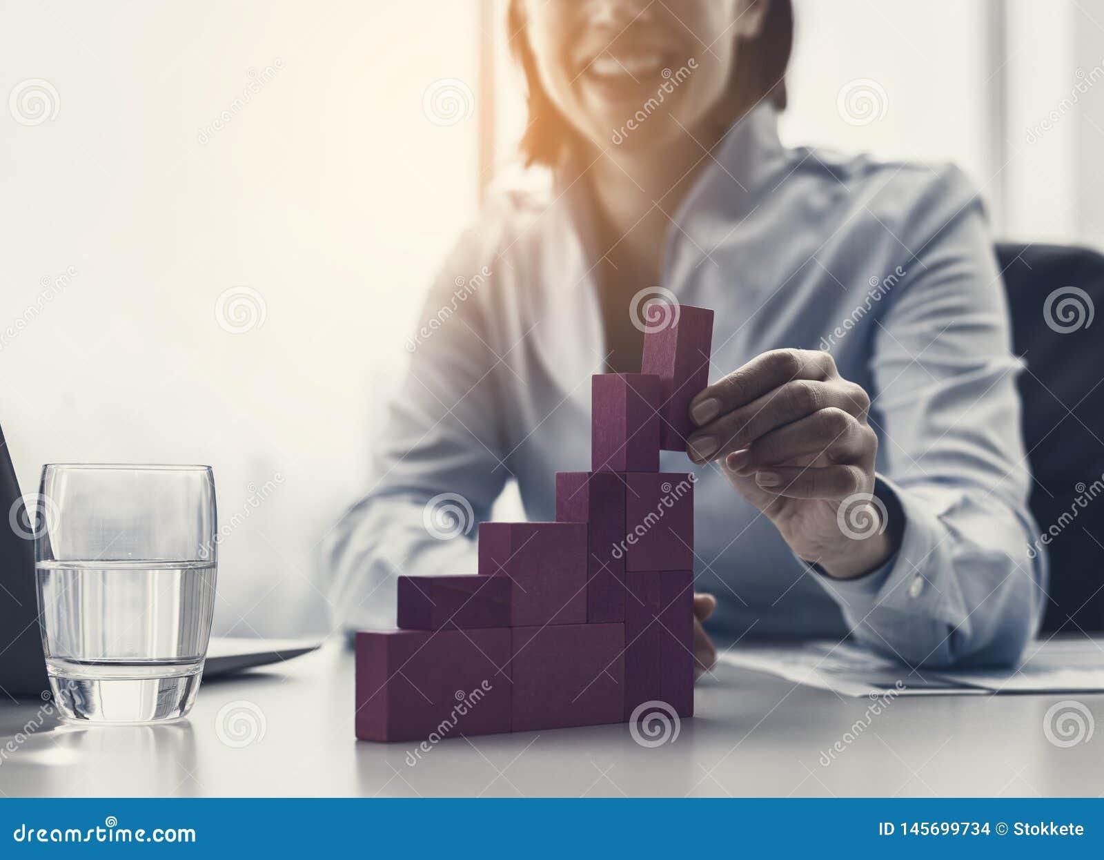 Lächelnde Geschäftsfrau, die ein erfolgreiches Finanzdiagramm errichtet
