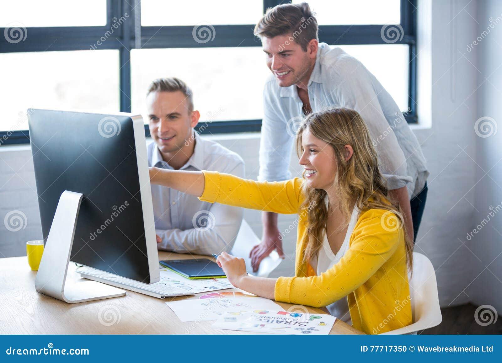 Lächelnde Geschäftsleute, die über Computer sich besprechen