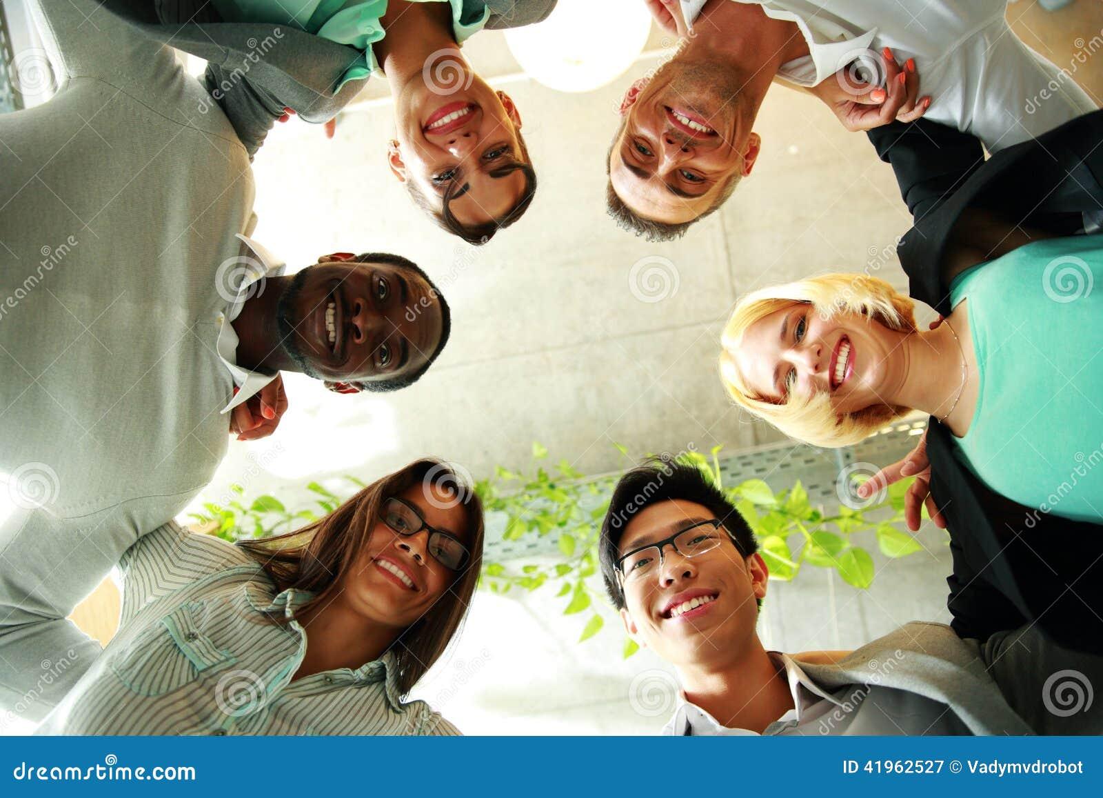 Lächelnde Geschäftsleute mit ihren Köpfen zusammen
