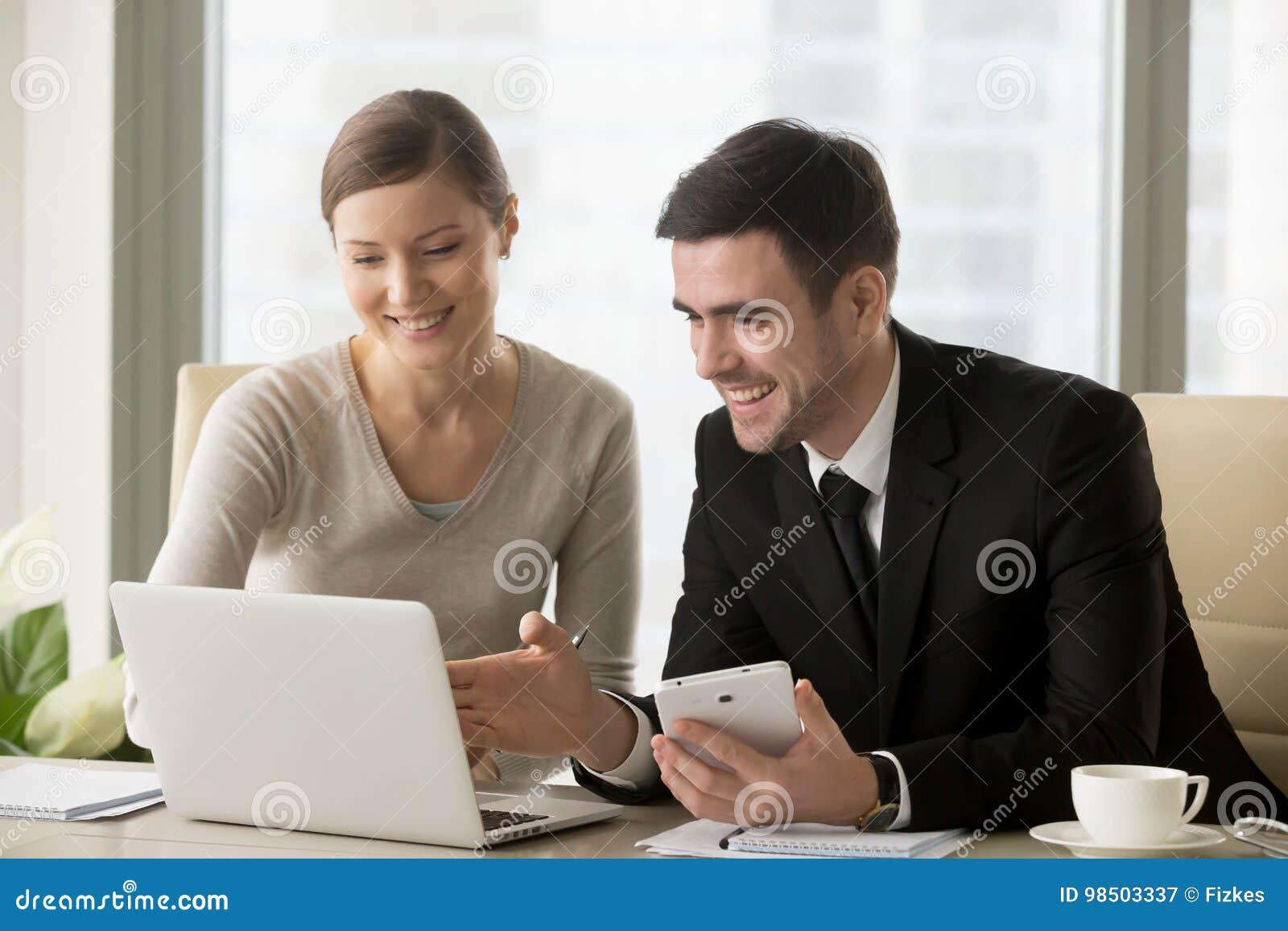 Lächelnde glückliche Wirtschaftler, die intelligente Geräte für bewegliches busi verwenden