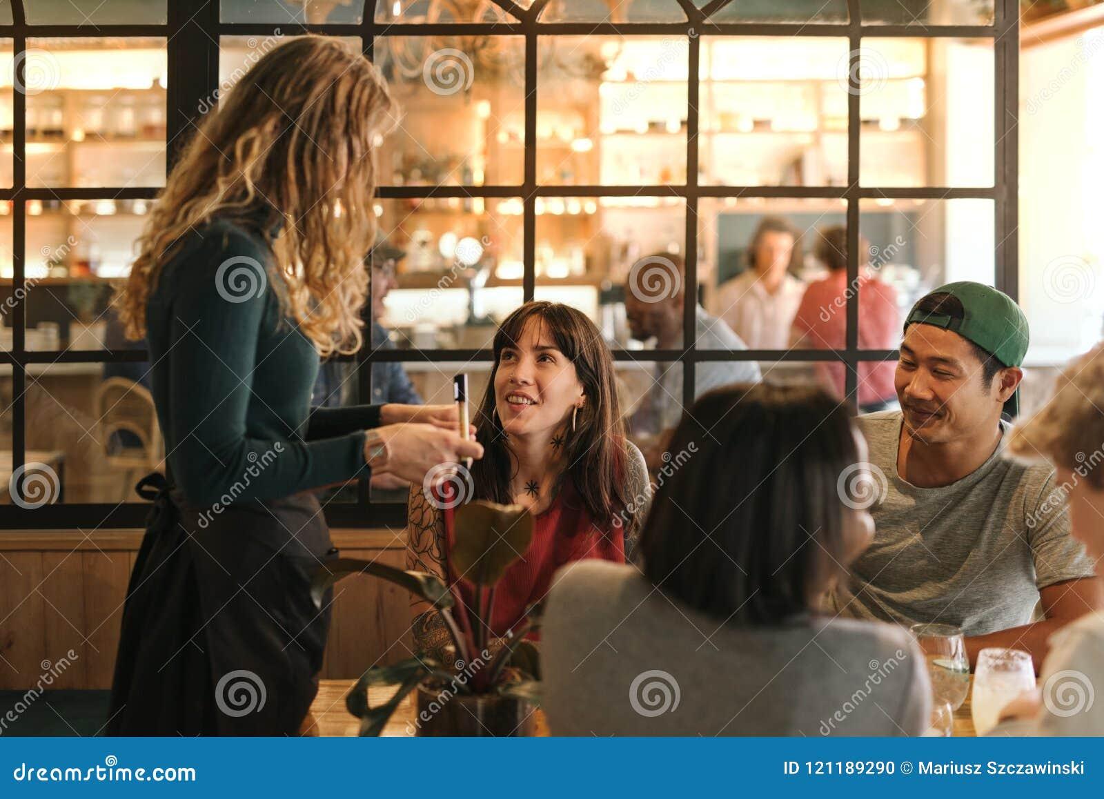 Lächelnde Gruppe Freunde, die Lebensmittel in einer Bistro bestellen