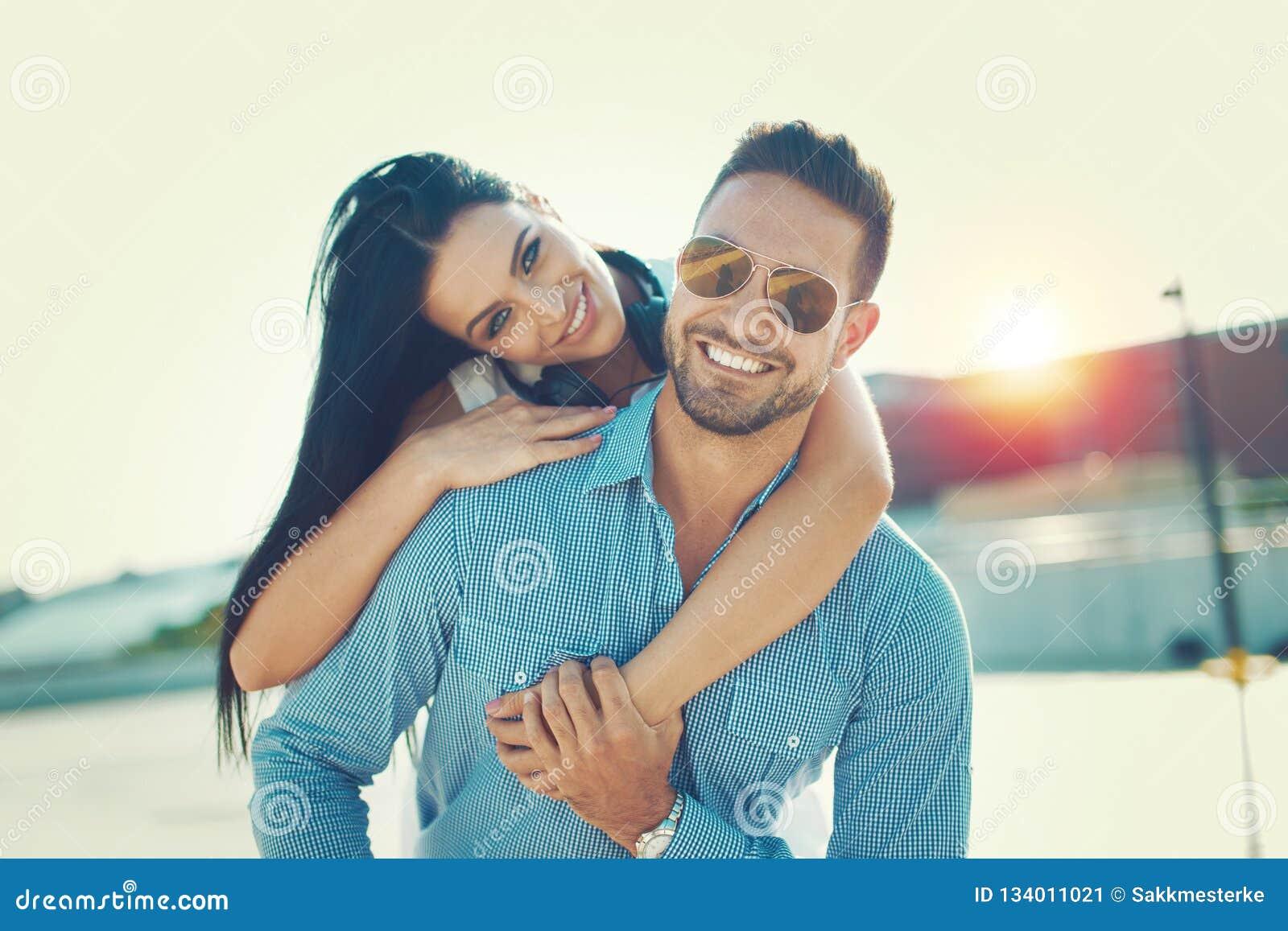 Lächelnde Haltung der glücklichen jungen Paare Doppelpolan den oudoors