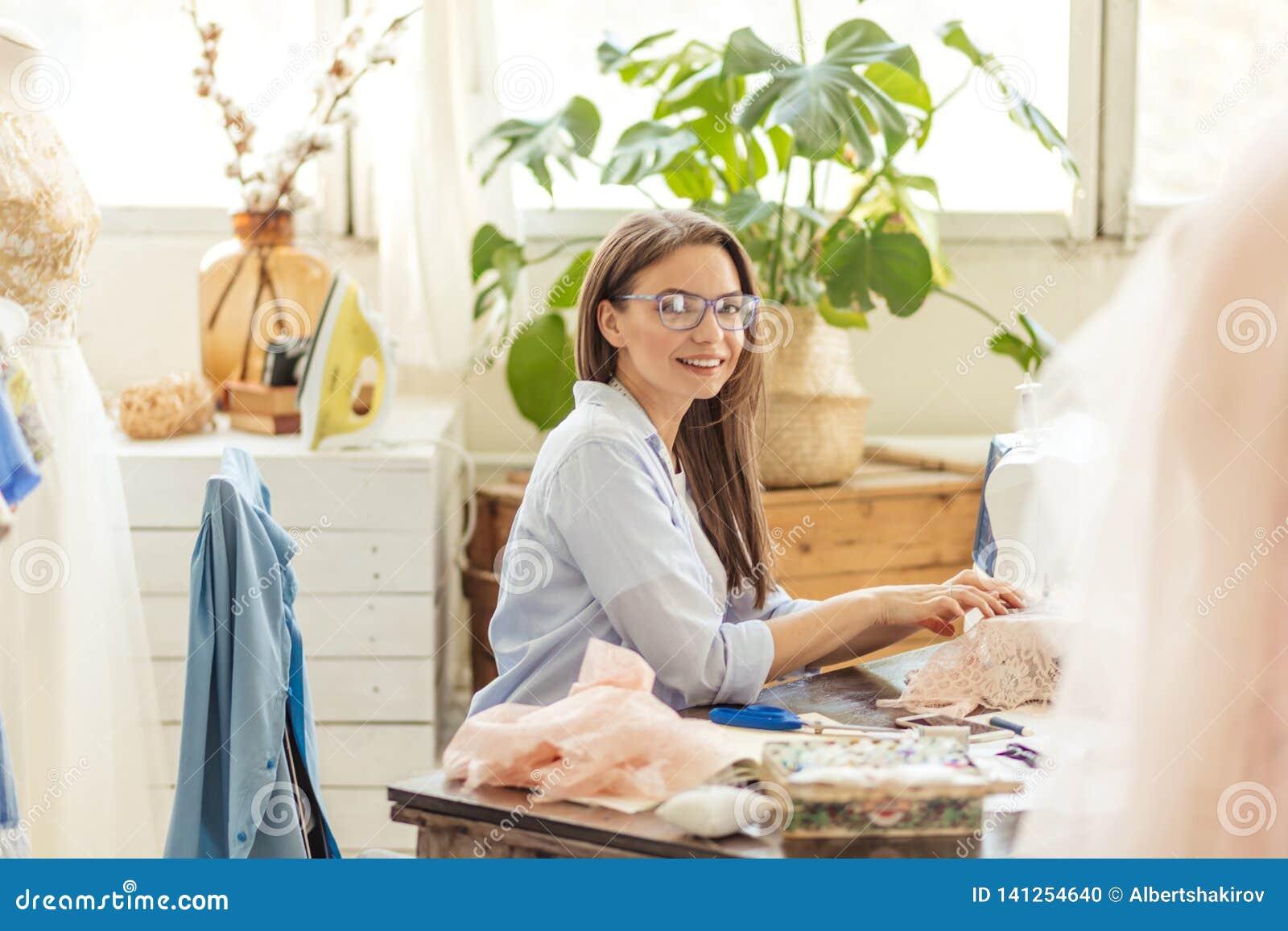 Lächelnde junge Damenschneiderinfrau näht Kleidung auf einer Nähmaschine in ihrer Werkstatt