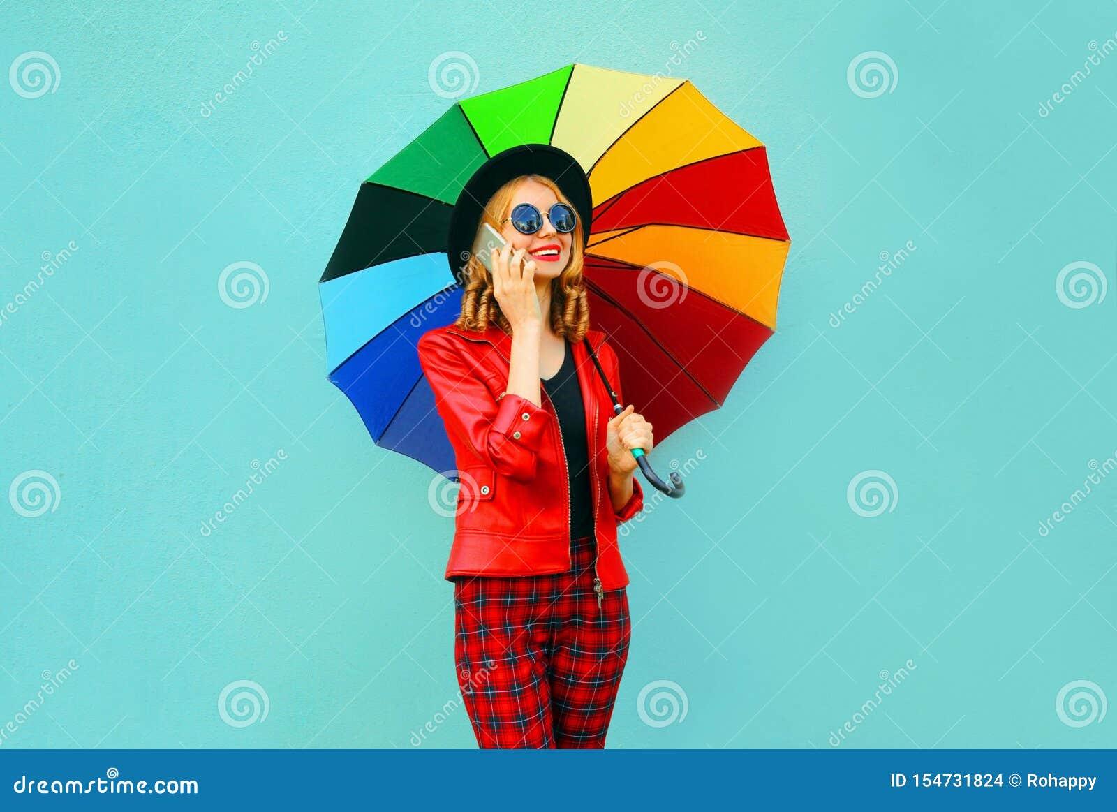 Lächelnde junge Frau des Porträts, die um Telefon mit buntem Regenschirm in der roten Jacke, schwarzer Hut auf blauer Wand ersuch