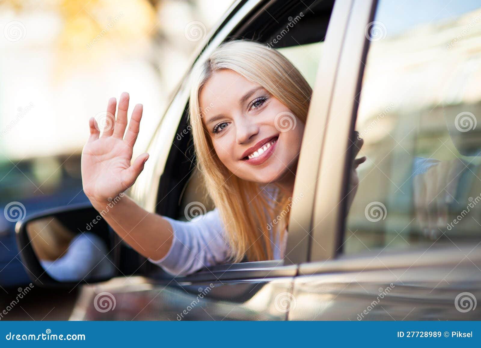 Lächelnde junge Frau, die im Auto sitzt