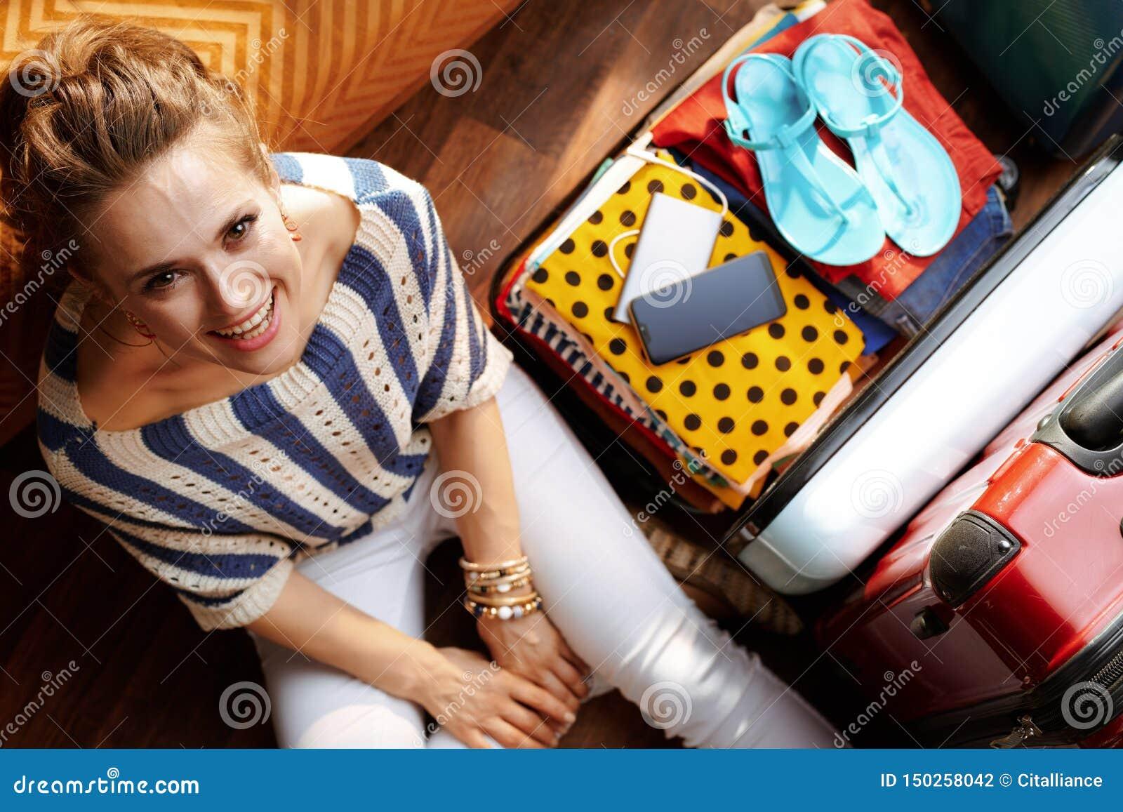 Lächelnde junge Frau im modernen Wohnzimmer am sonnigen Sommertag