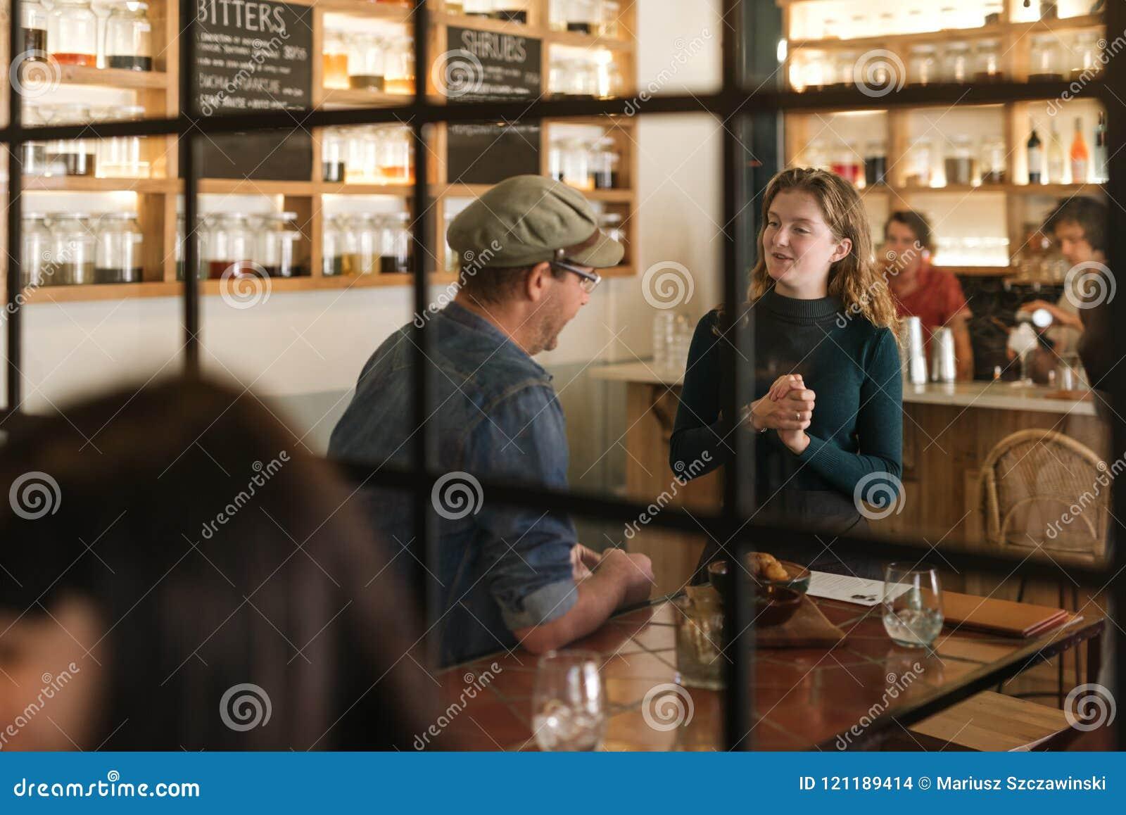 Lächelnde junge Kellnerin, die mit einem Bistrokunden spricht