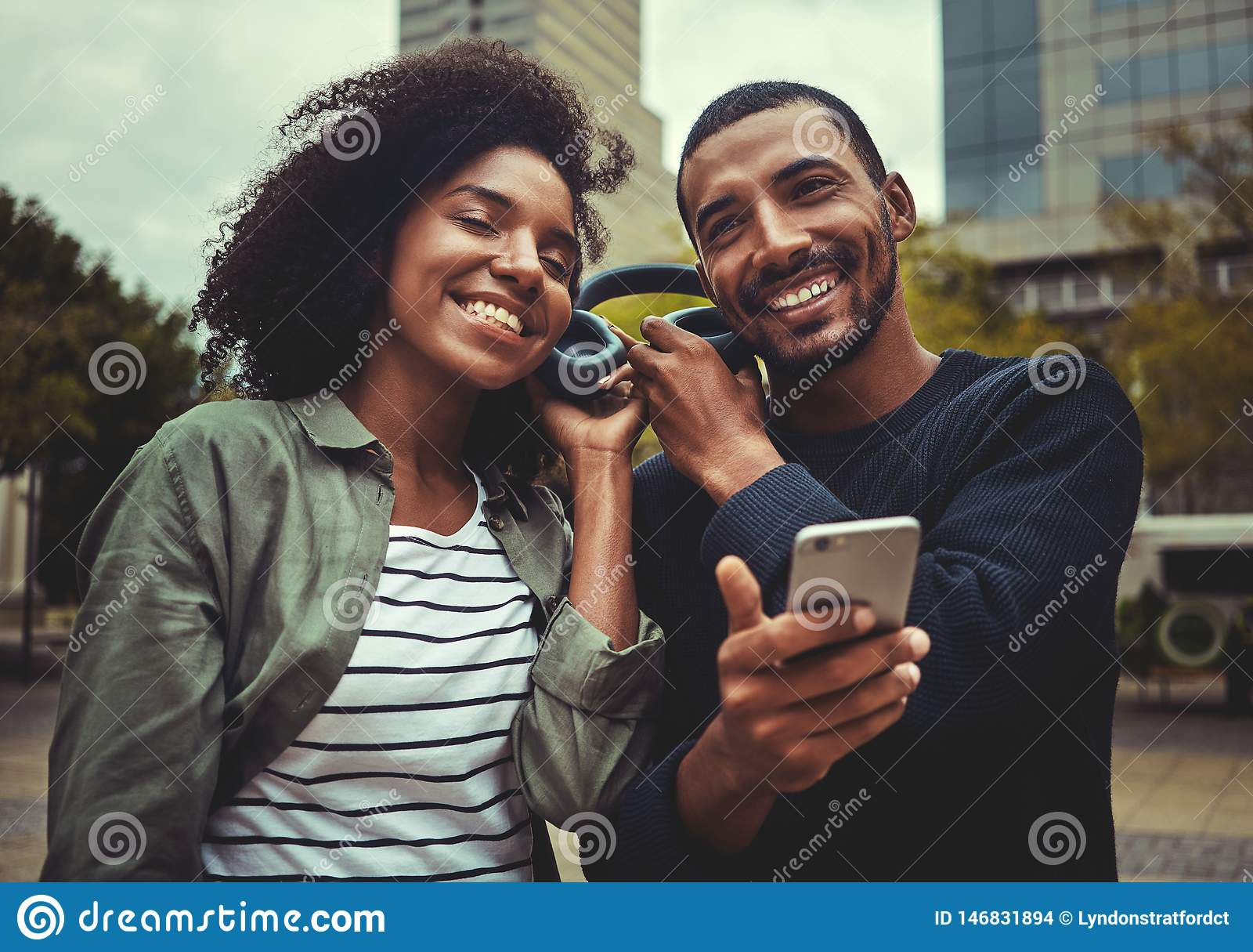 Lächelnde junge Paare, die das Hören Musik auf einem Kopfhörer genießen