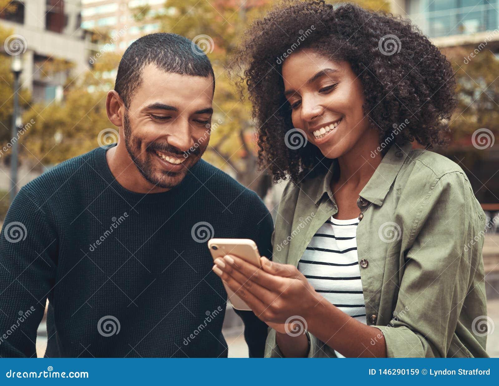 Lächelnde junge Paare, die Smartphone betrachten