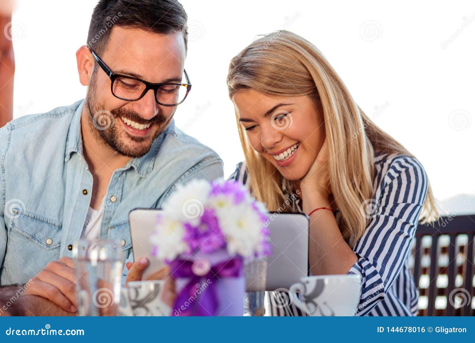 Lächelnde junge Paare unter Verwendung einer Tablette im Café