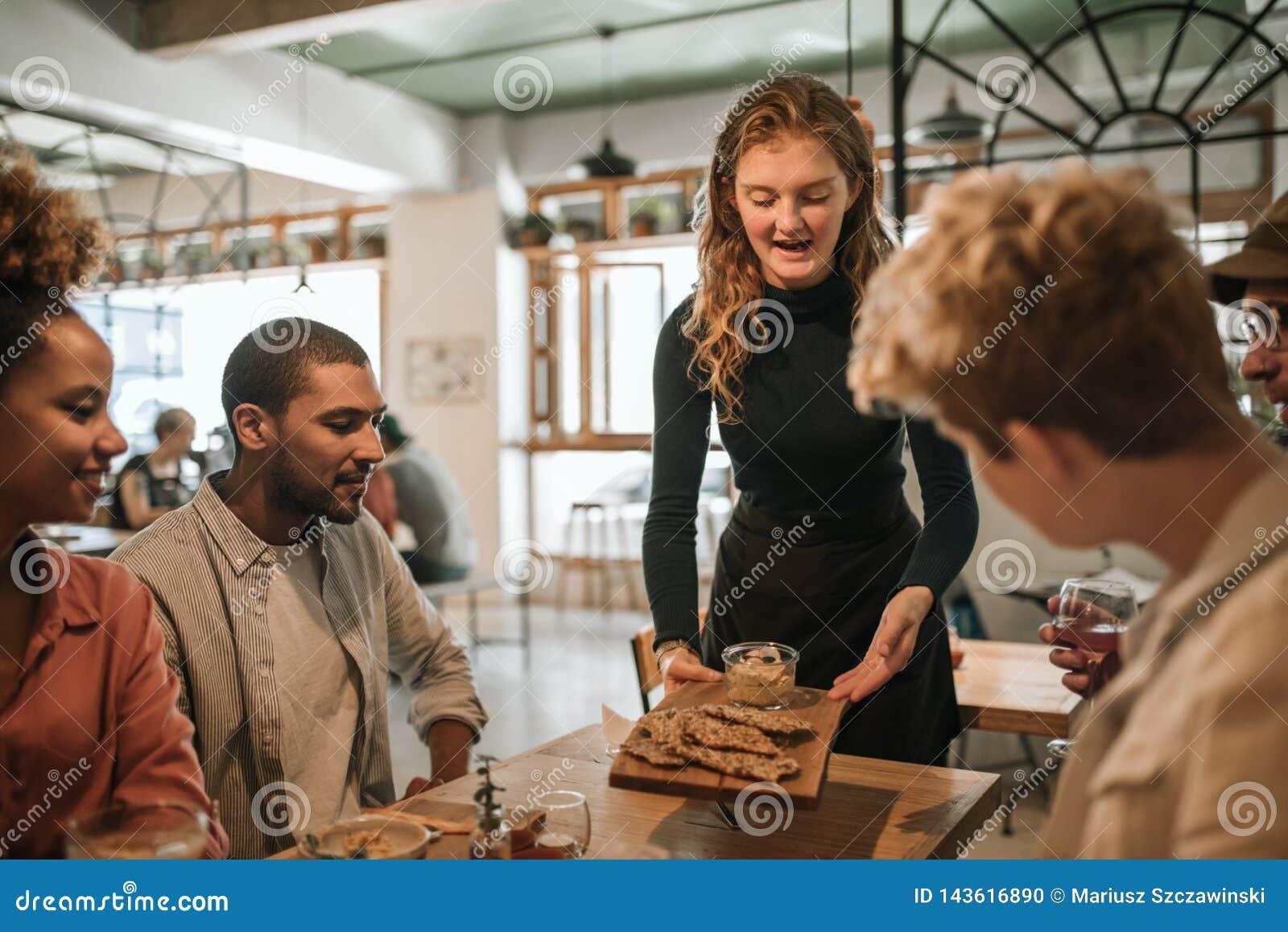 Lächelnde Kellnerin, die Nahrung zu einem Tabelle von Kunden holt