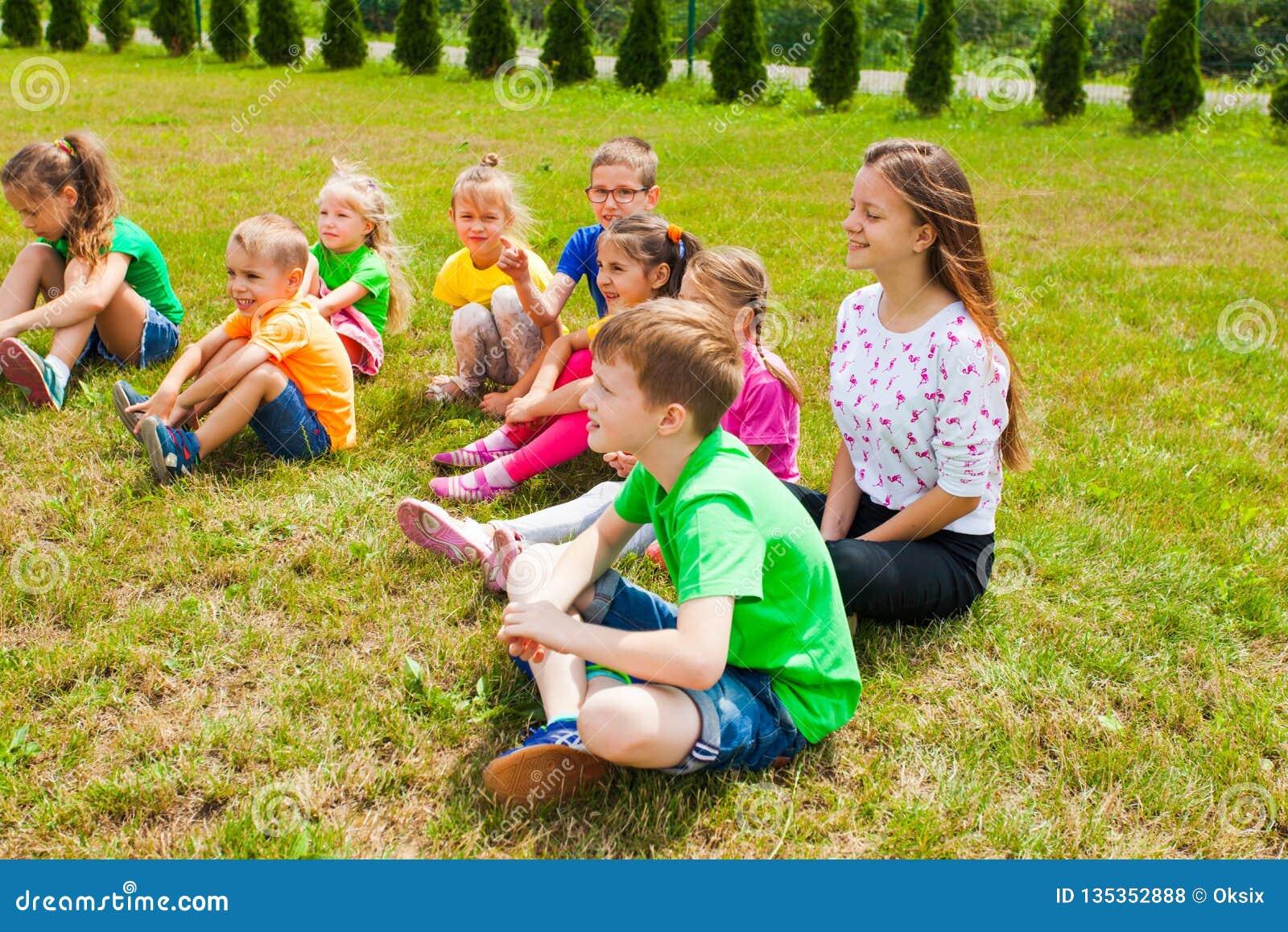 Lächelnde Kinder, die auf einem Gras Lektion an der im Freien sitzen