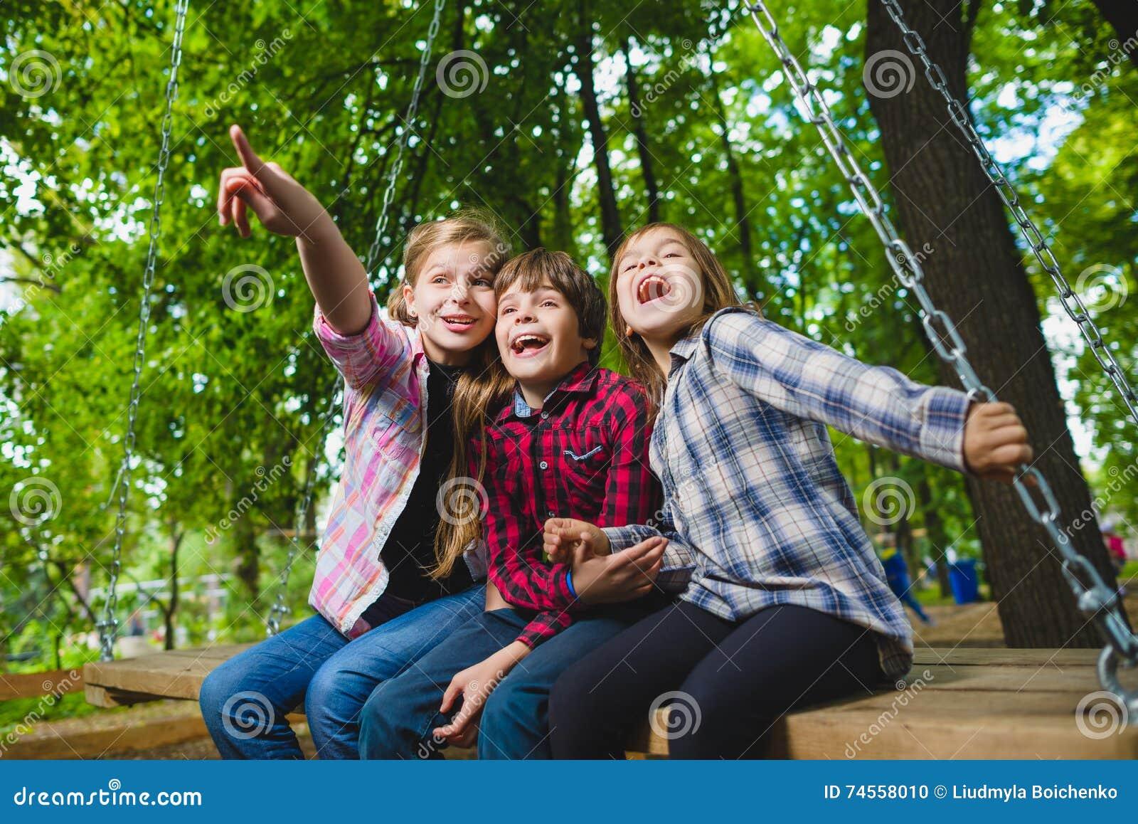 l chelnde kinder die spa am spielplatz haben kinder die drau en im sommer spielen jugendliche. Black Bedroom Furniture Sets. Home Design Ideas