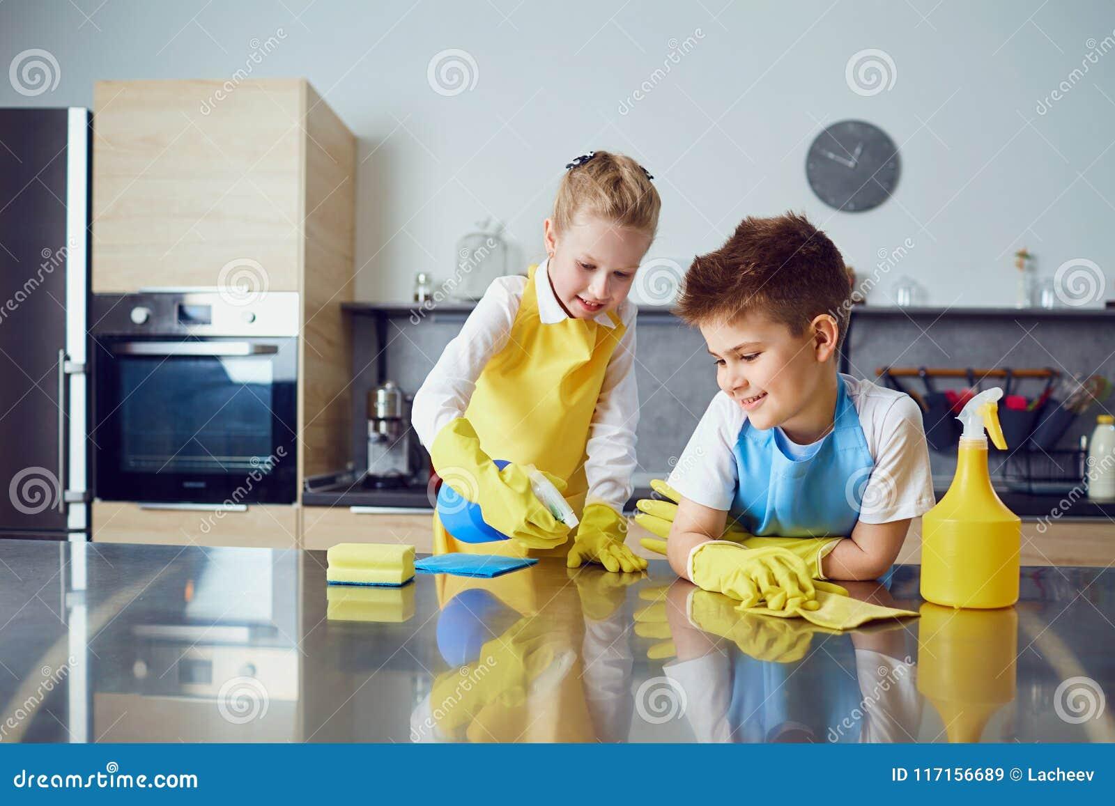 Lächelnde Kinder tun die Reinigung in der Küche
