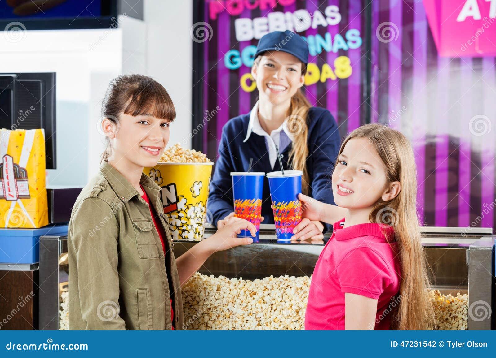 Lächelnde Mädchen, die Popcorn und Getränke von kaufen