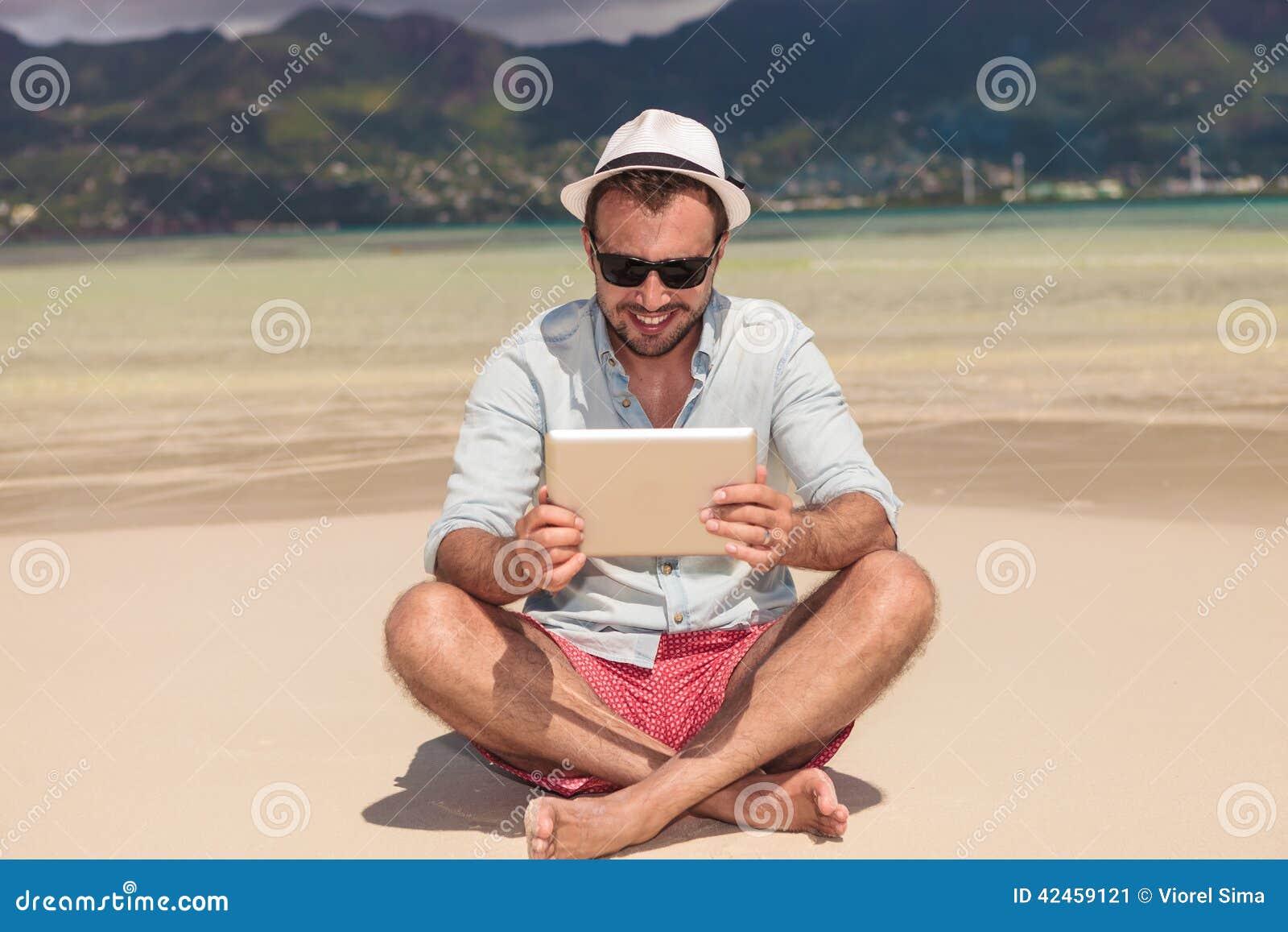 Lächelnde Mannlesung auf Tablette beim den Strand sich hinsetzen