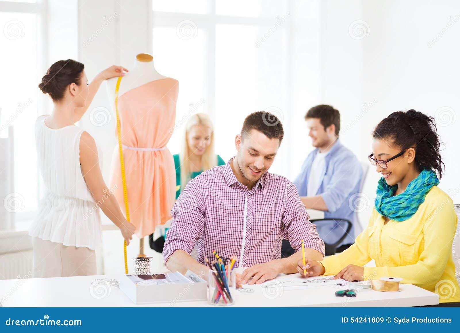Lächelnde Modedesigner, die im Büro arbeiten