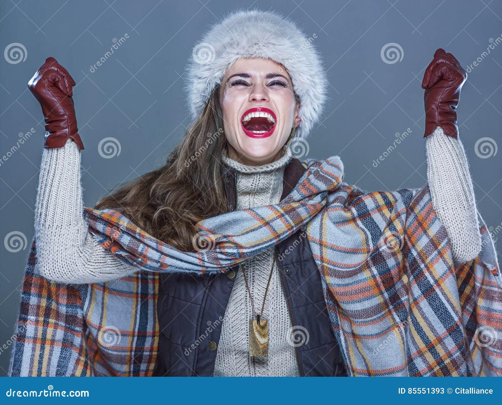 Lächelnde moderne Frau im Pelzhut lokalisiert auf dem kalten blauen Freuen