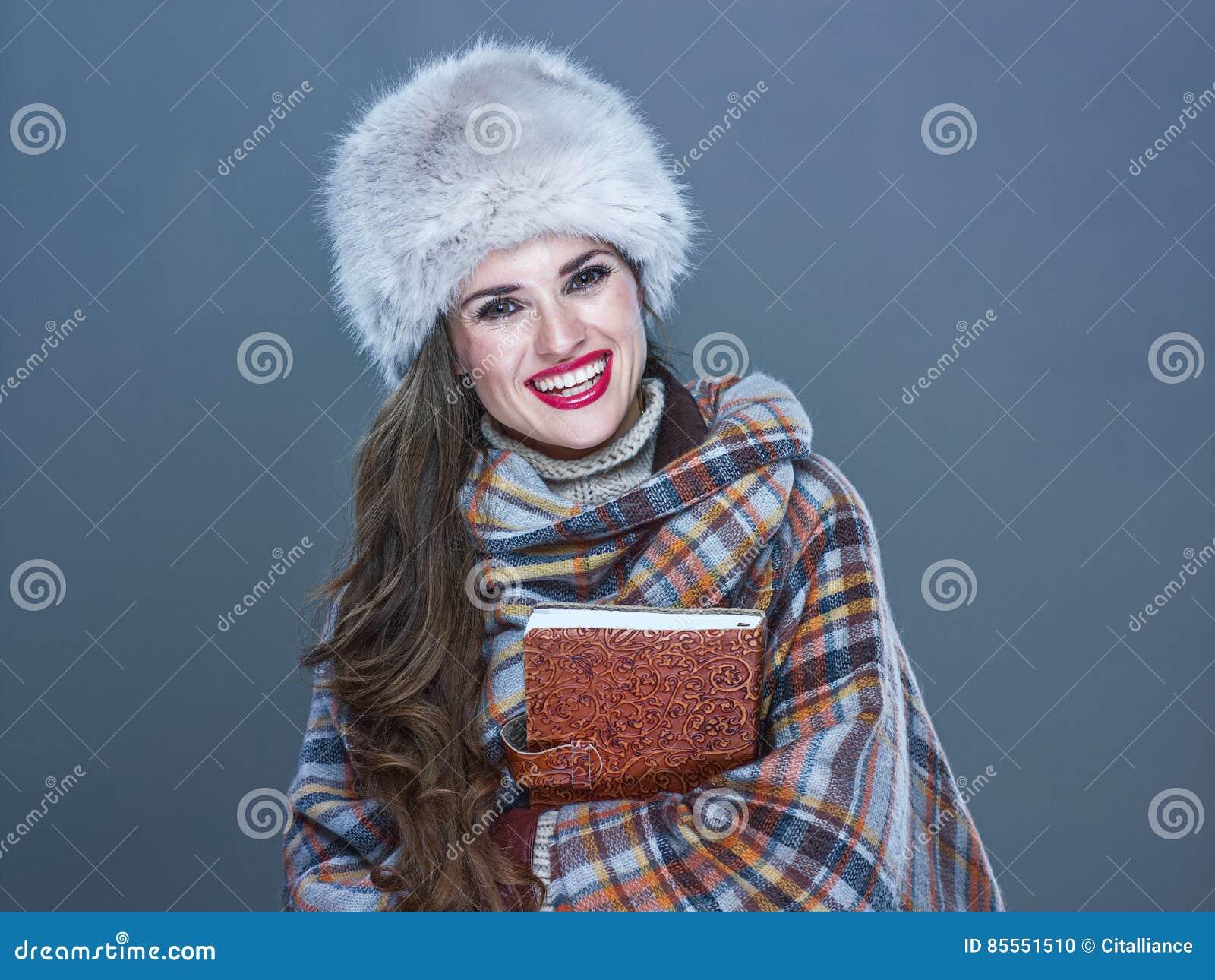 Lächelnde moderne Frau im Pelzhut lokalisiert auf der kalten blauen Umfassung