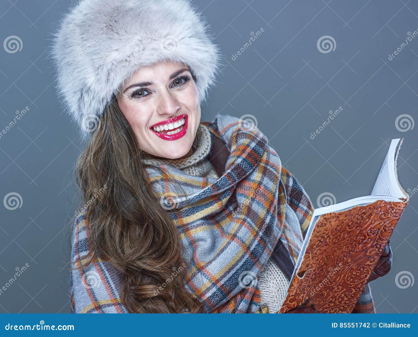 Lächelnde modische Frau lokalisiert auf kaltem blauem Hintergrund mit Buch