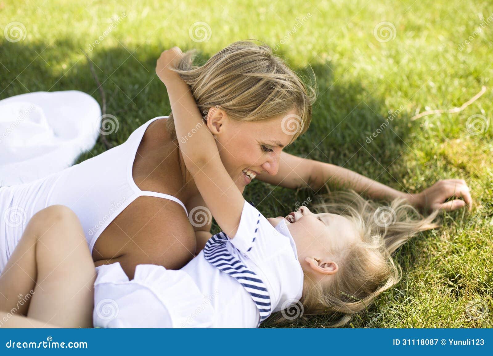 Lächelnde Mutter und kleine Tochter auf Natur. Glückliche Menschen draußen