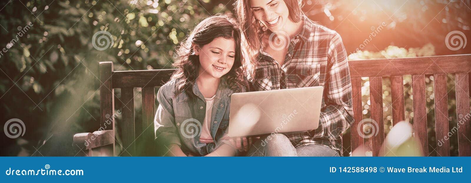 Lächelnde Mutter und Tochter, die Laptop beim Sitzen auf Holzbank verwendet