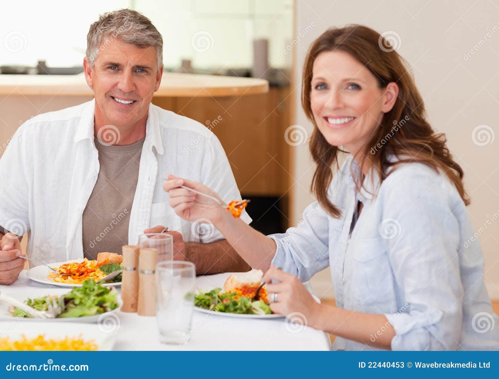 Lächelnde Paare, die Abendessen essen