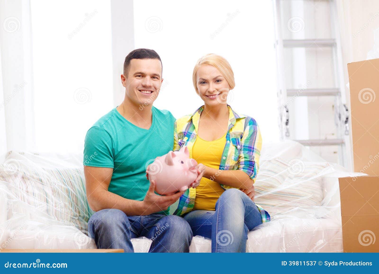 Lächelnde Paare mit piggybank im neuen Haus